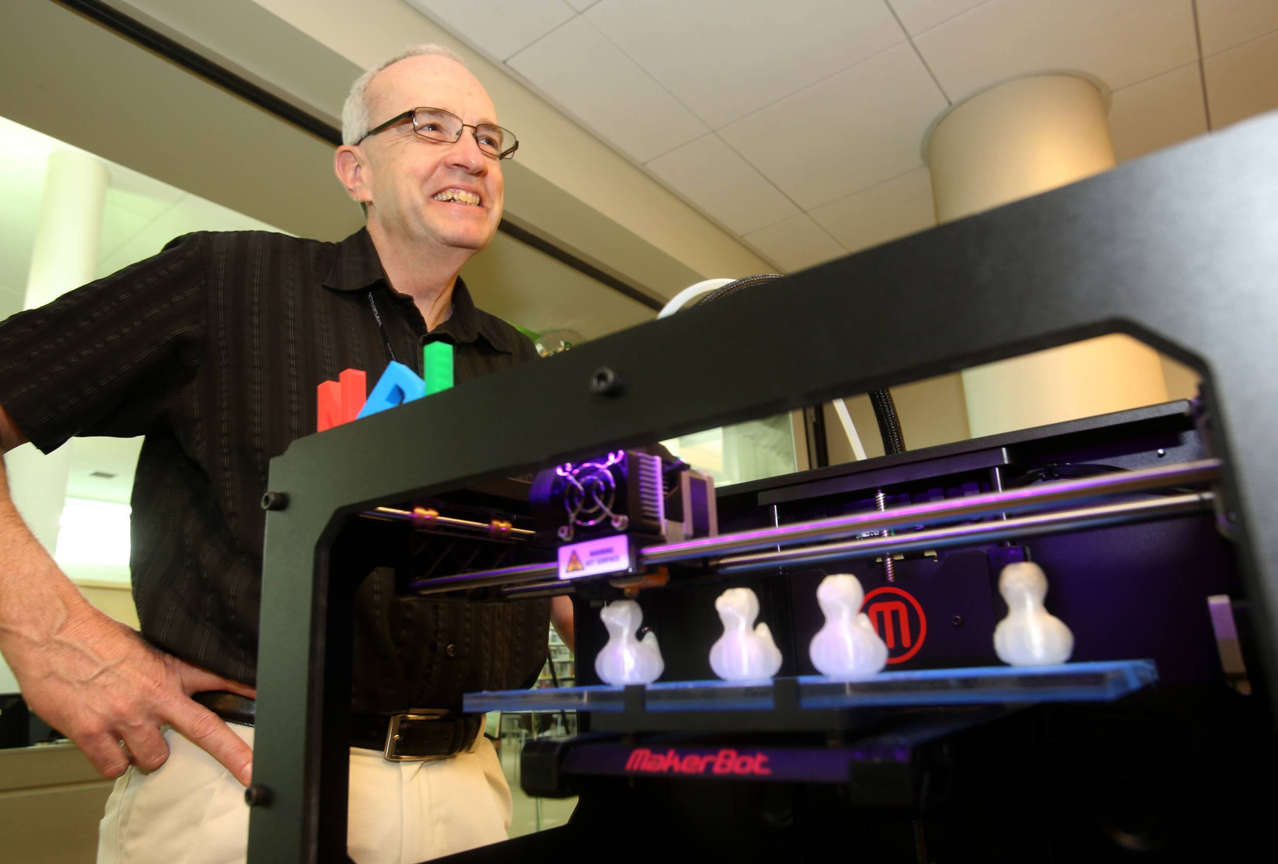 Naperville Public Library help desk employee Jeff Smallwood is one of many staff members who can help card holders use a 3-D printer the library has installed in its new Idea Lab at the 95th Street Library.