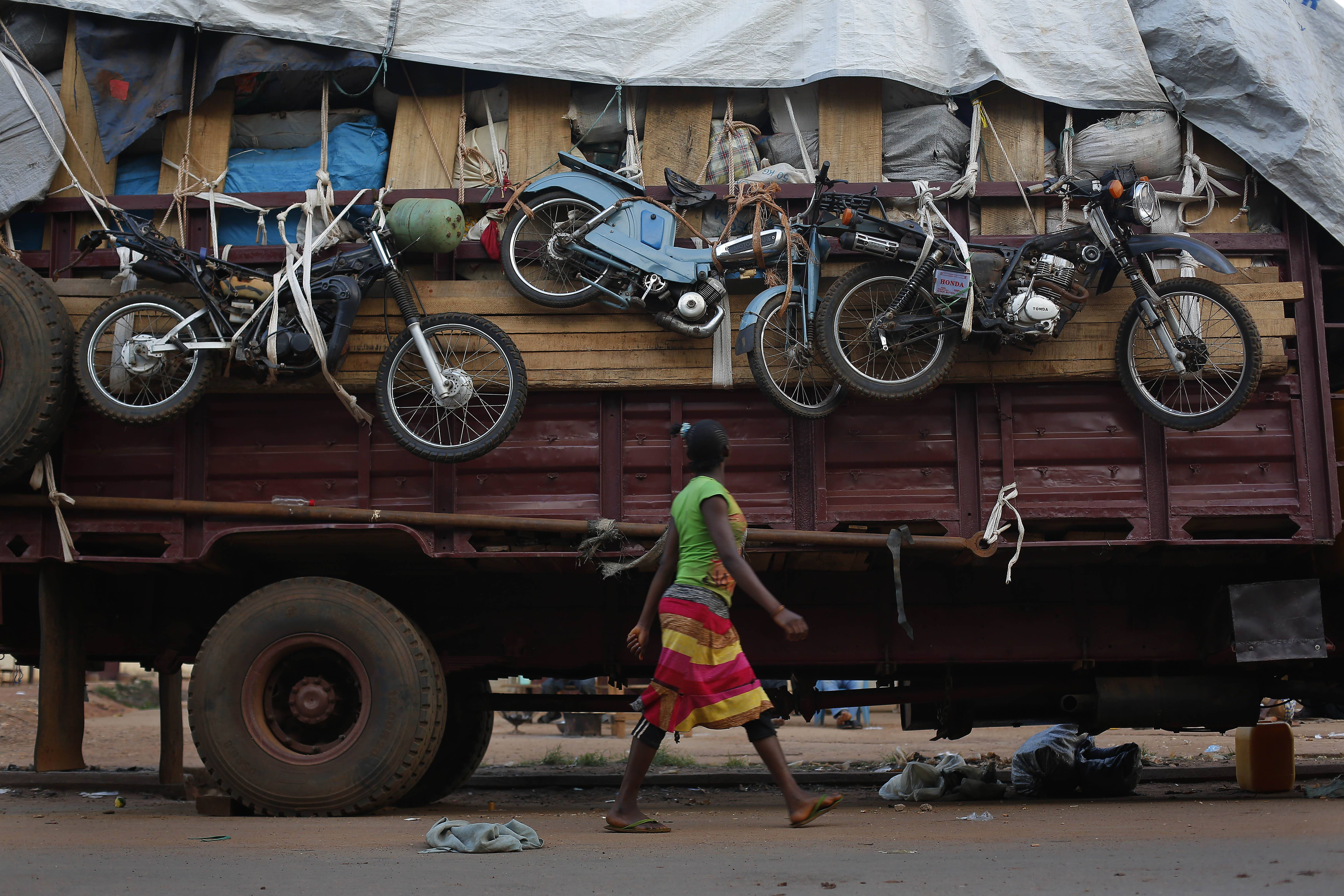 A woman walks past a truck waiting to leave for Chad loaded with goods belonging to Muslim residents of the PK5 district of Bangui, Central African Republic, Wednesday April 9, 2014.