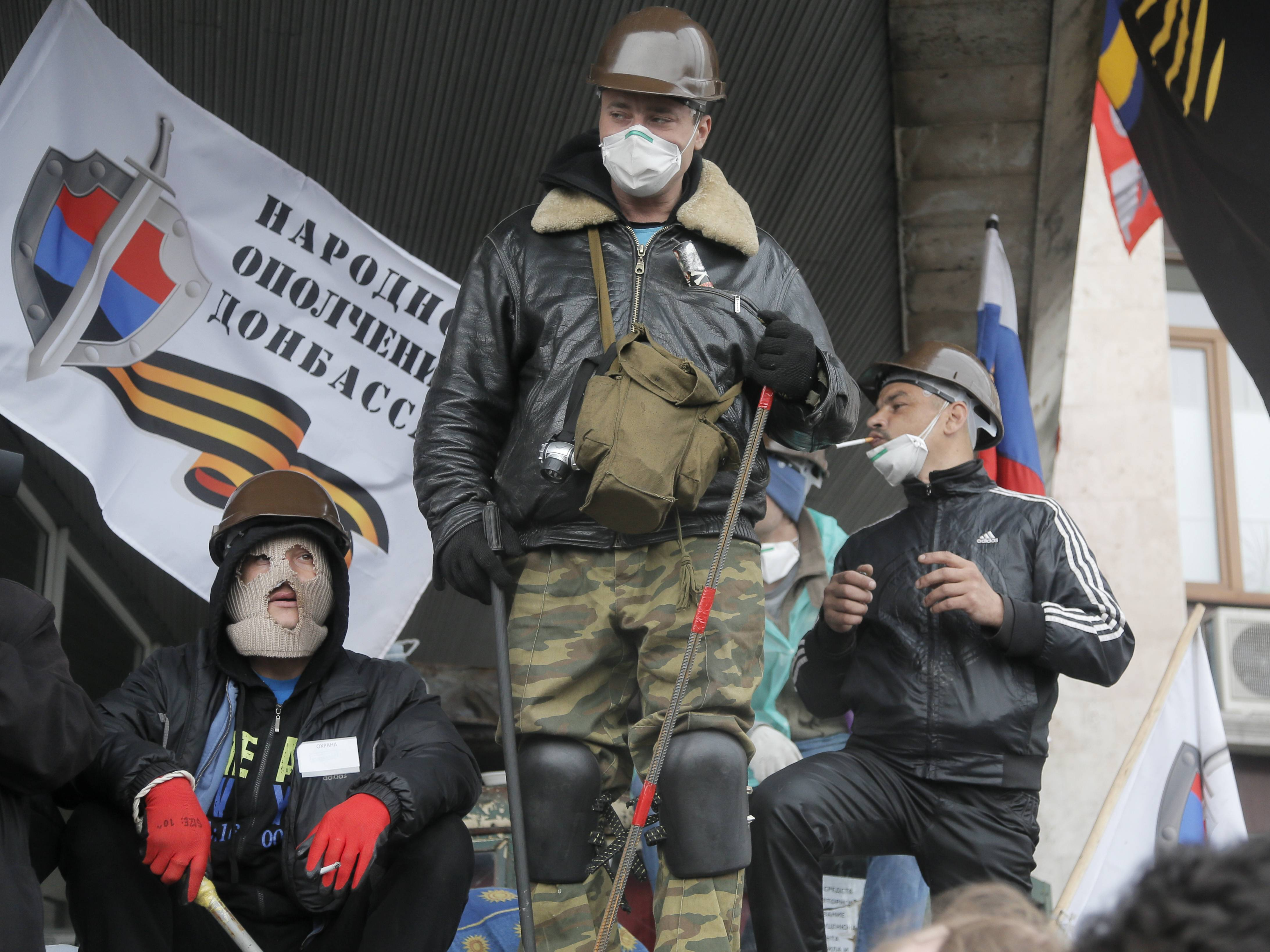 Masked pro-Russian activists seated on top of a barricade as they guard a regional administration building that they had seized earlier in Donetsk, Ukraine, Thursday. The text on the flag reads: Militia of Donbass.