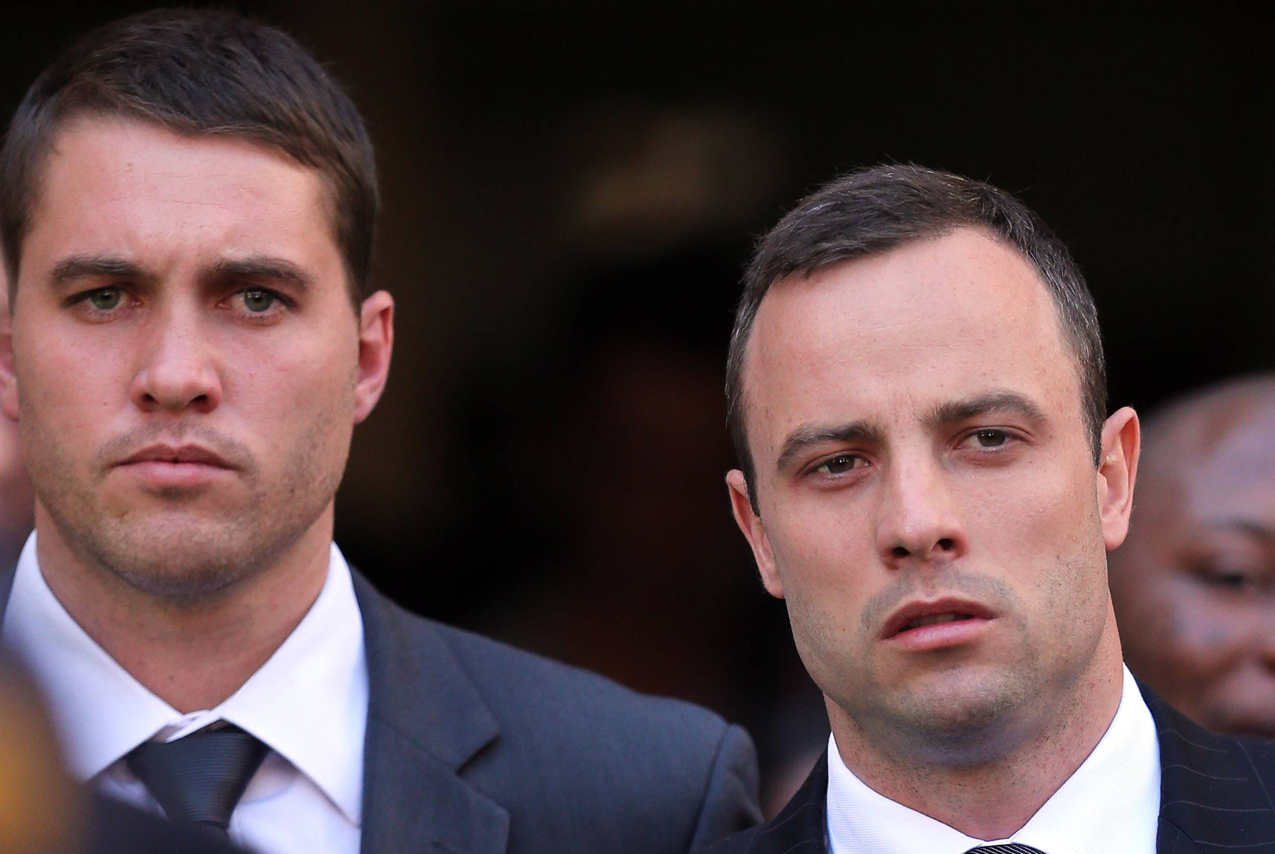 Oscar Pistorius, right, leaves the high court in Pretoria, South Africa, Thursday. The prosecution in Paralympic athlete's murder trial said he was lying and adapting his version of events on the morning he shot his model girlfriend Reeva Steenkamp to line up with the evidence.