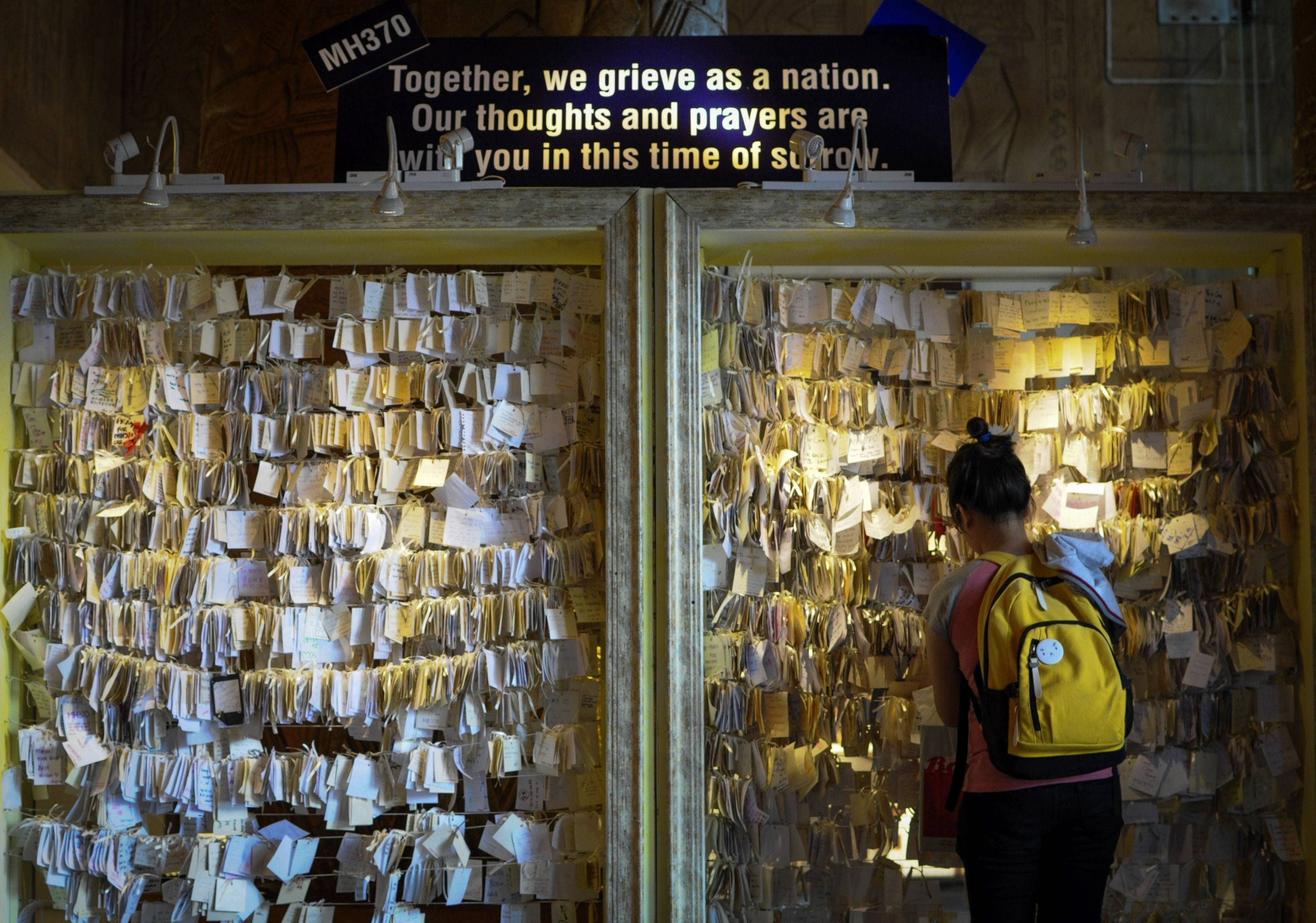 A woman ties a message card for passengers onboard the missing Malaysia Airlines Flight 370 at a shopping mall in Petaling Jaya, near Kuala Lumpur, Malaysia, Thursday.