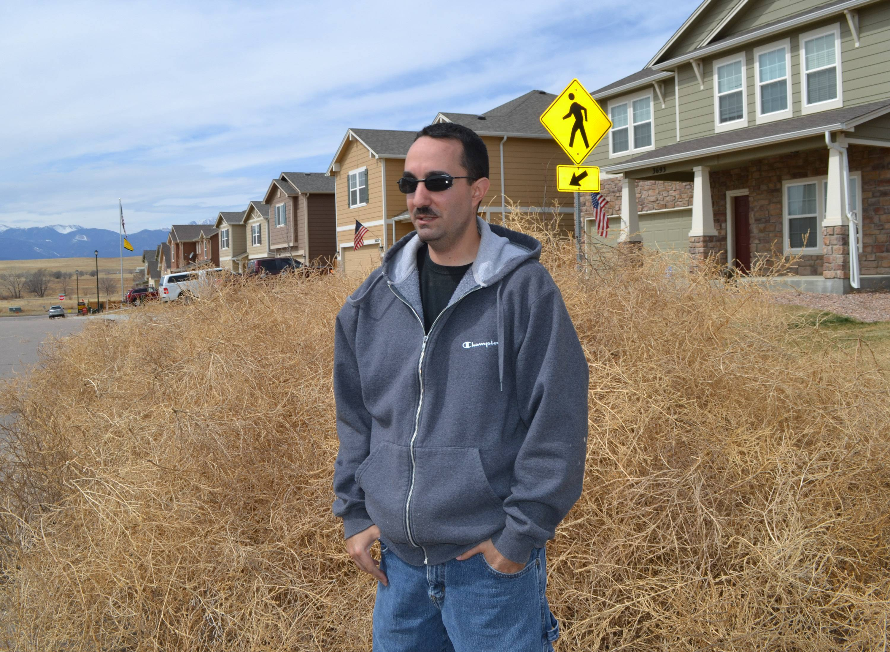 Chris Talbott stands with a pile of tumbleweed in front of his home in Colorado Springs, Colo. Parts of Colorado are being overrun with tumbleweeds because of the drought affecting much of the western United States.