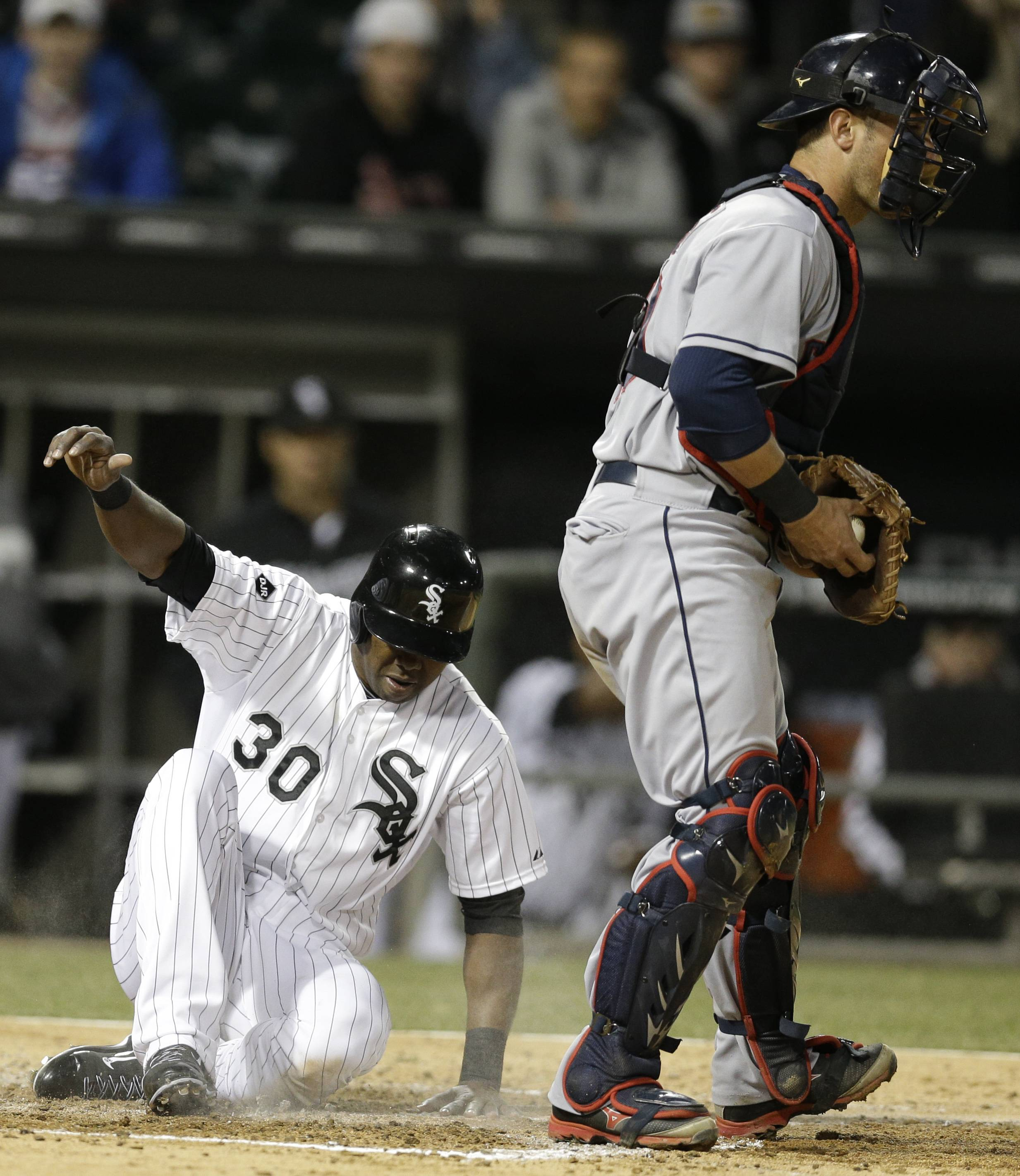 Chicago White Sox's Alejandro De Aza, left, scores past Cleveland Indians catcher Yan Gomes during the fourth inning of a baseball game in Chicago, Thursday, April 10, 2014.