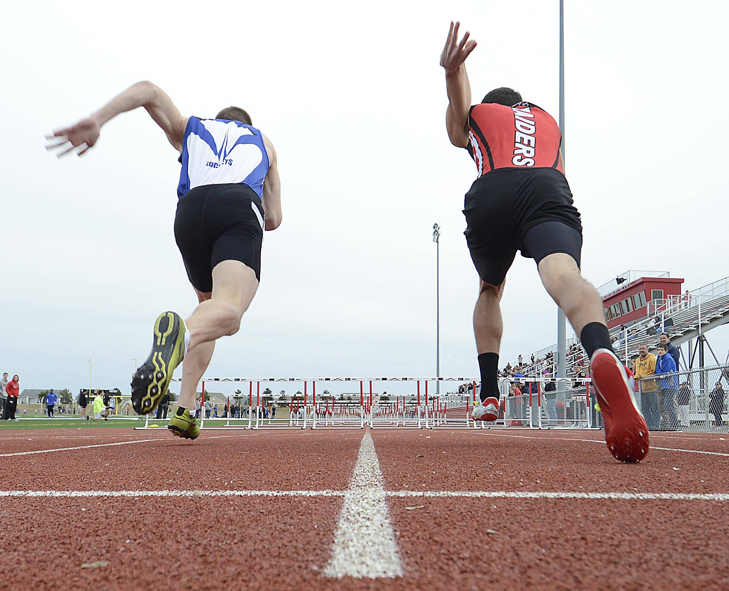 Burlington Central's Sean Kish and Huntley's Brennan Bell, right, jump out of the blocks at the start of the 110-meter high Hurdles on Thursday at the Huntley boys track invitational.