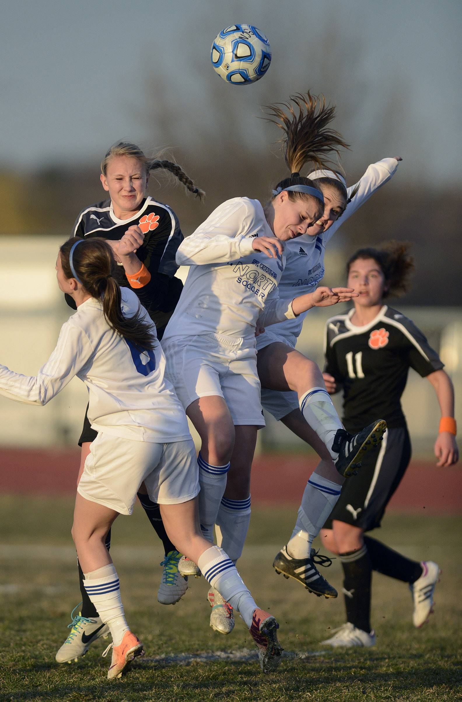Wheaton Warrenville South's Allison Harvey (left, black jersey) and St. Charles North's Alyssa Brandt, center, and Taylor Sypien, right bounce off each other as they fight to receive the ball in the first half on Thursday, April 10.