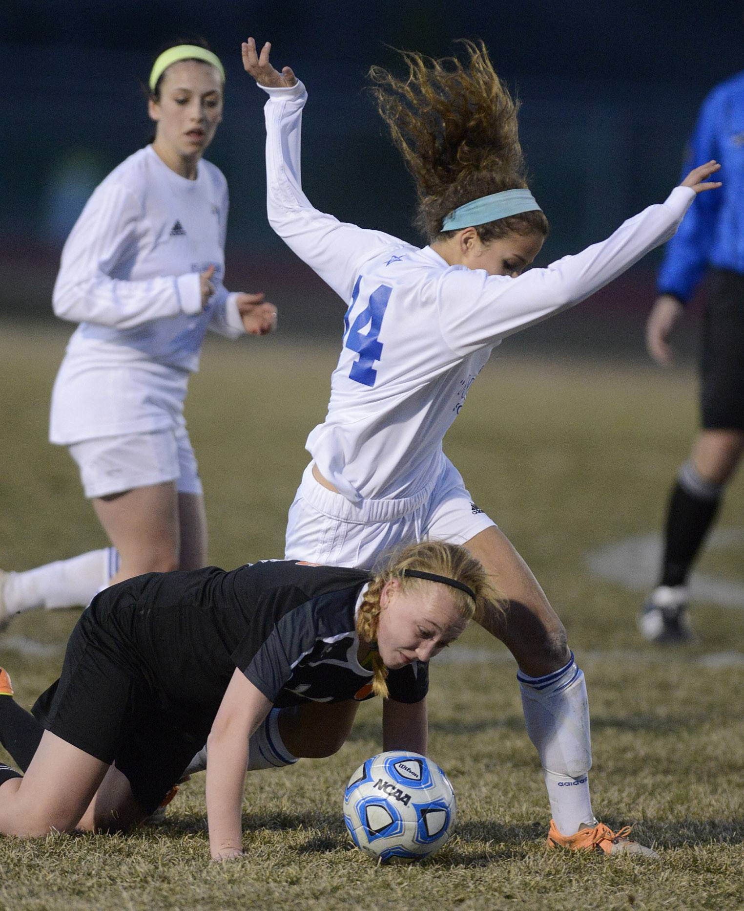 Wheaton Warrenville South's Sarah Burns tries to get upright after stumbling while St. Charles North's Lizzie Parrilli almost tumbles during a scuffle for the ball in the first half on Thursday, April 10.