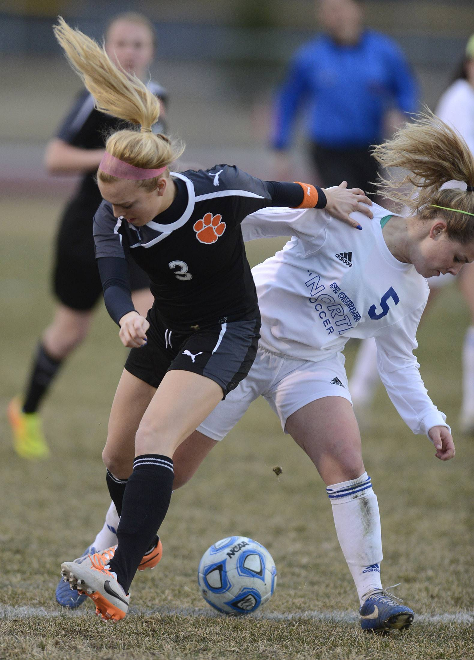Wheaton Warrenville South's Ava Fickle, left, and St. Charles North's Hanna Durocher battle for the ball in the first half on Thursday, April 10.