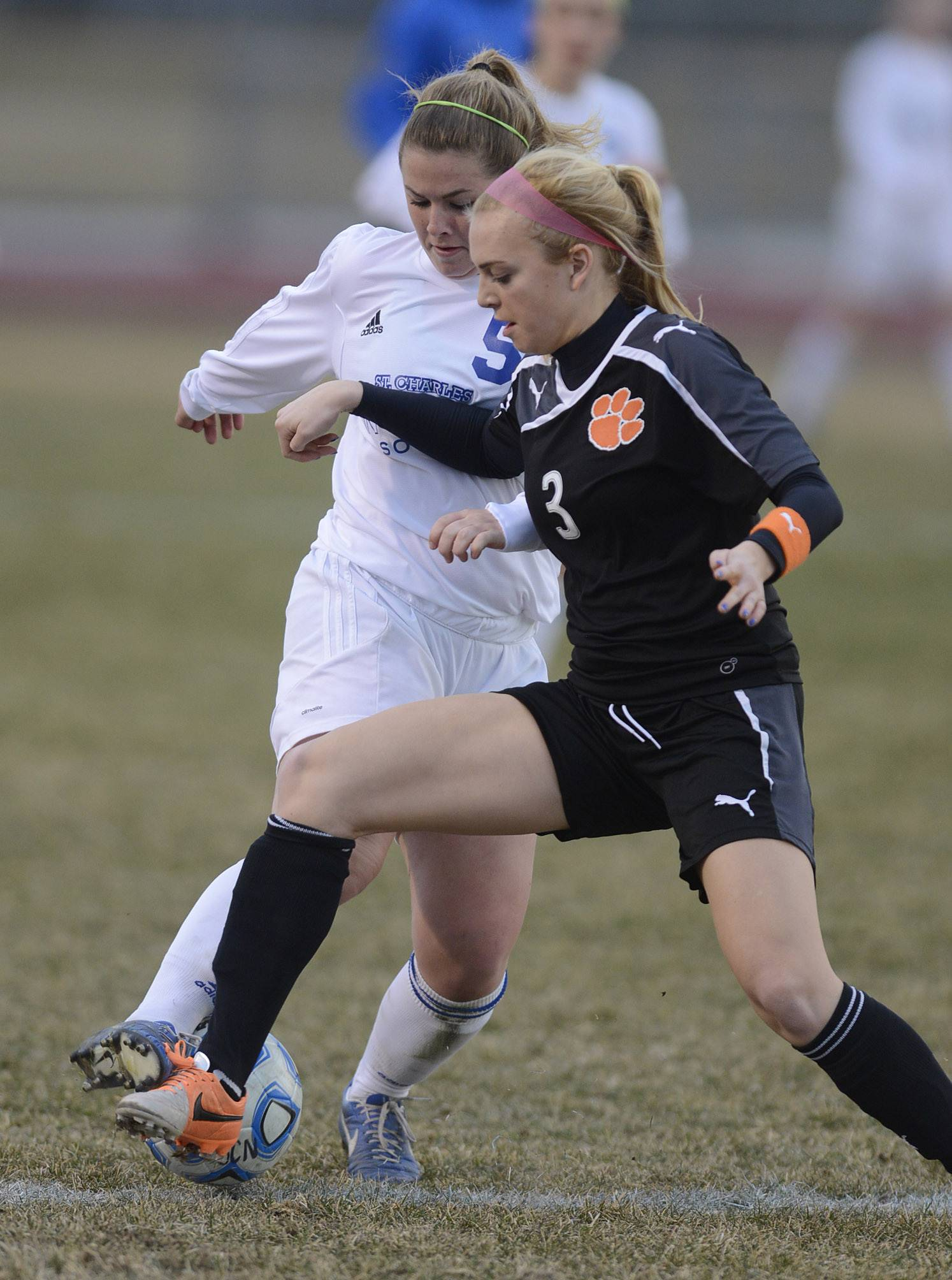 St. Charles North's Hanna Durocher, left, and Wheaton Warrenville South's Ava Fickle battle for the ball in the first half on Thursday, April 10.