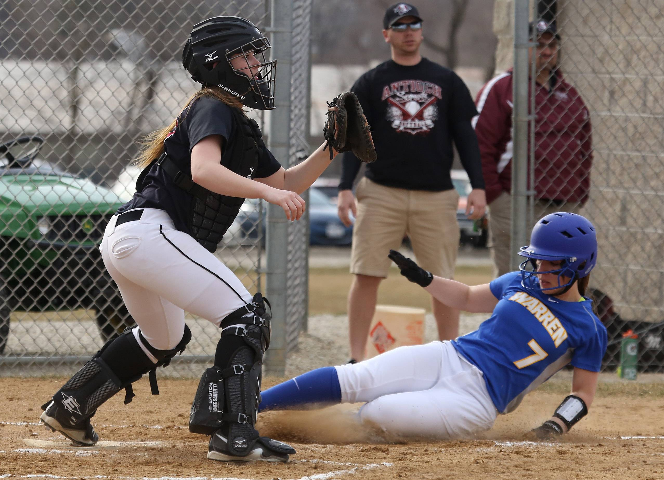 Warren's Jensen Plata slides safely into home past the tag of Antioch catcher Jessica Tyrell after a double steal on Thursday at Antioch.