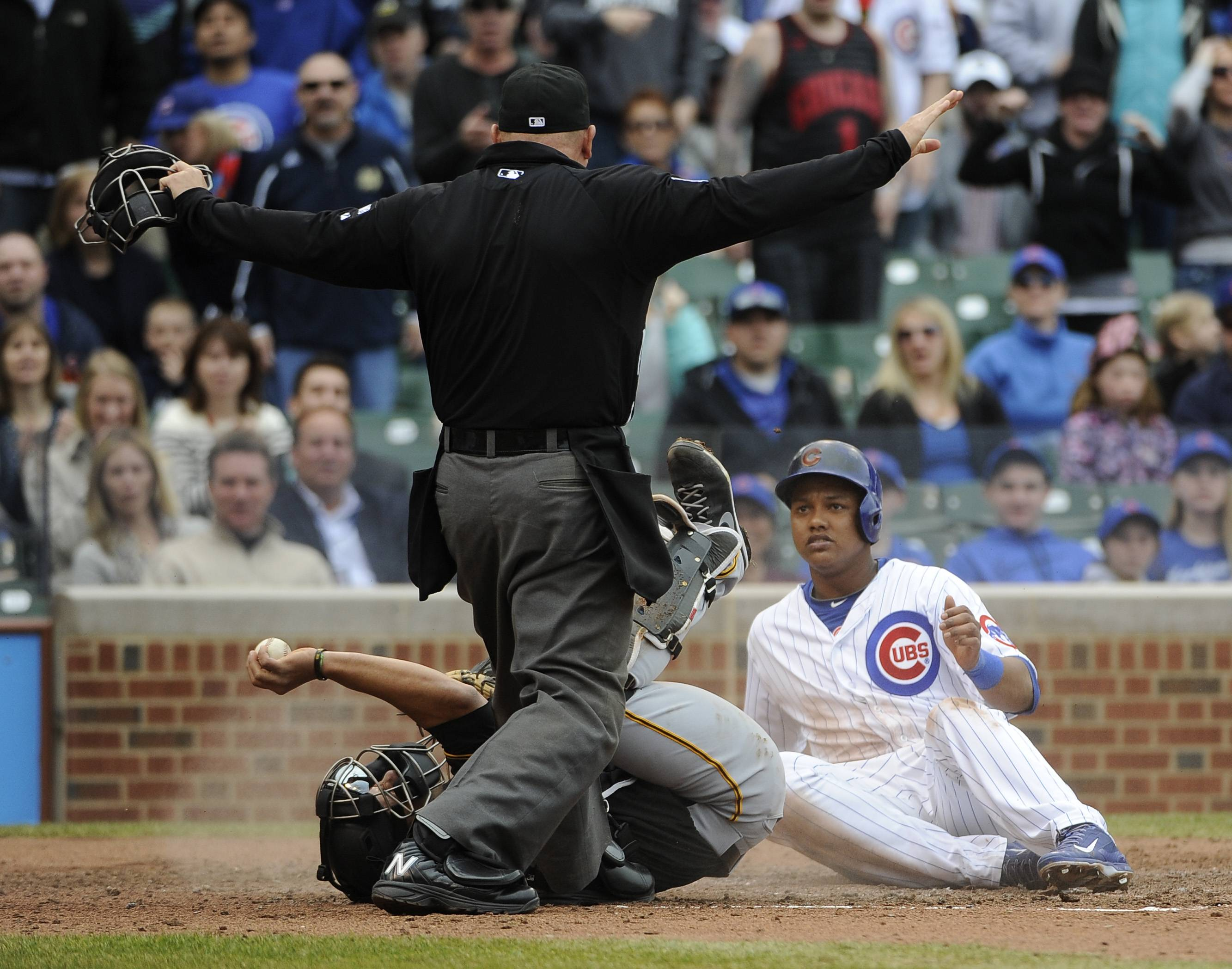 Starlin Castro, right, is called safe at home by umpire Mark Carlson, center, as Pittsburgh Pirates catcher Tony Sanchez, left,  falls over after making a late tag during the fourth inning of a baseball game on Thursday, April 10, 2014, in Chicago.