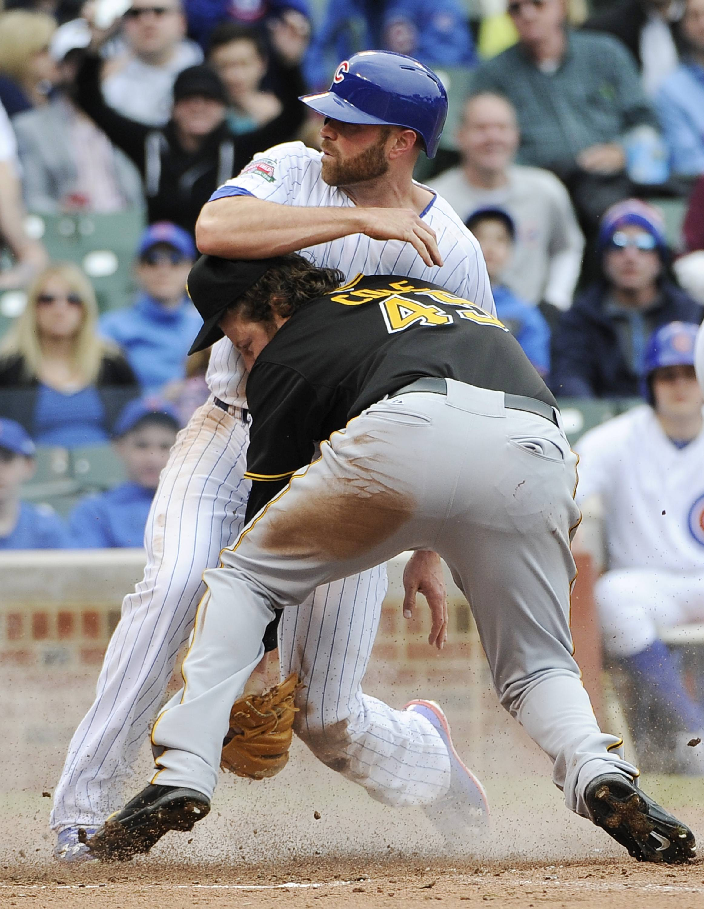 Nate Schierholtz, top, scores on a wild pitch as Pittsburgh Pirates starting pitcher Gerrit Cole (45) makes a late tag during the fourth inning of a baseball game on Thursday, April 10, 2014 in Chicago.