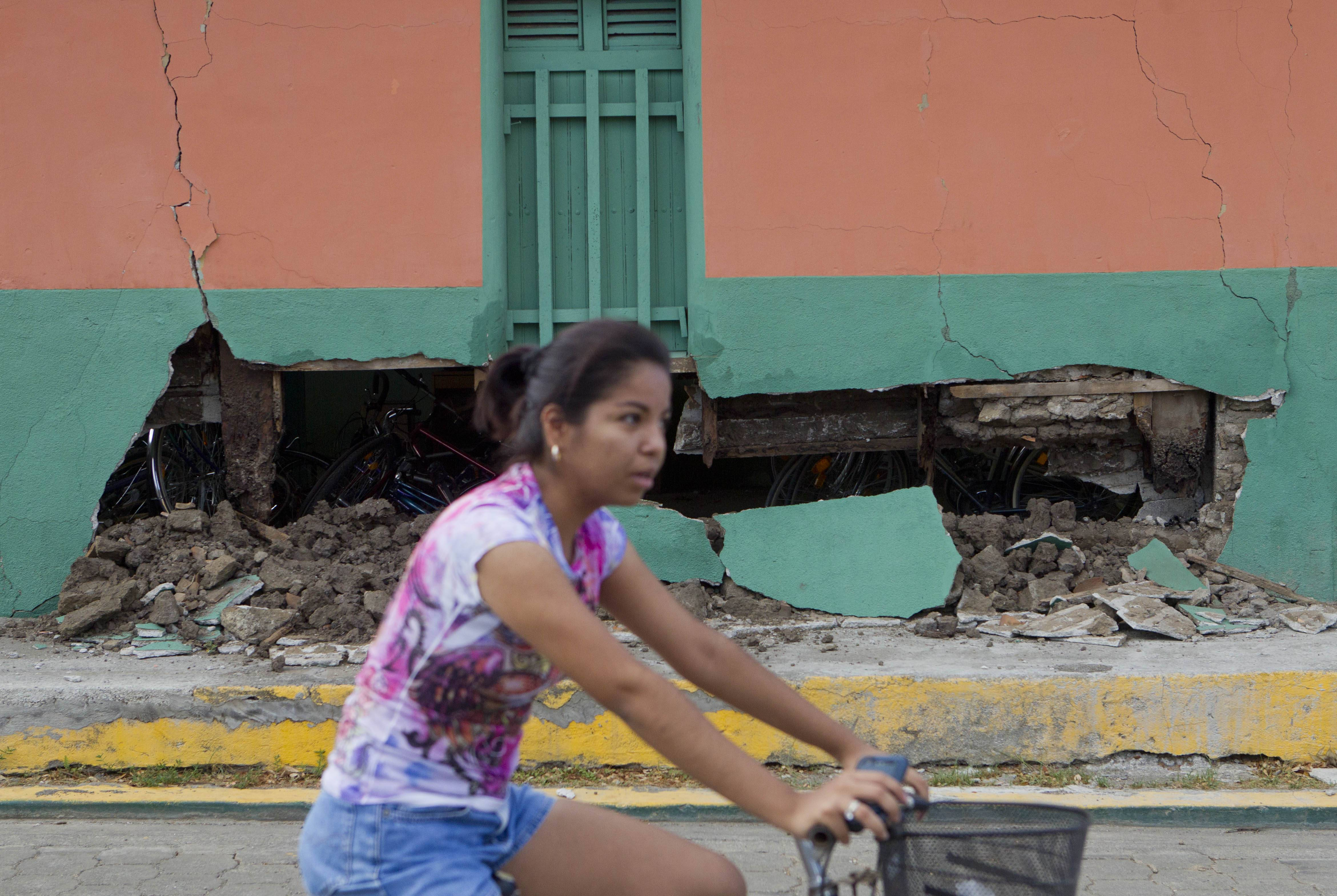 A girl passes by on a bicycle Friday, in front a home damaged by an earthquake in Nagarote, Nicaragua.