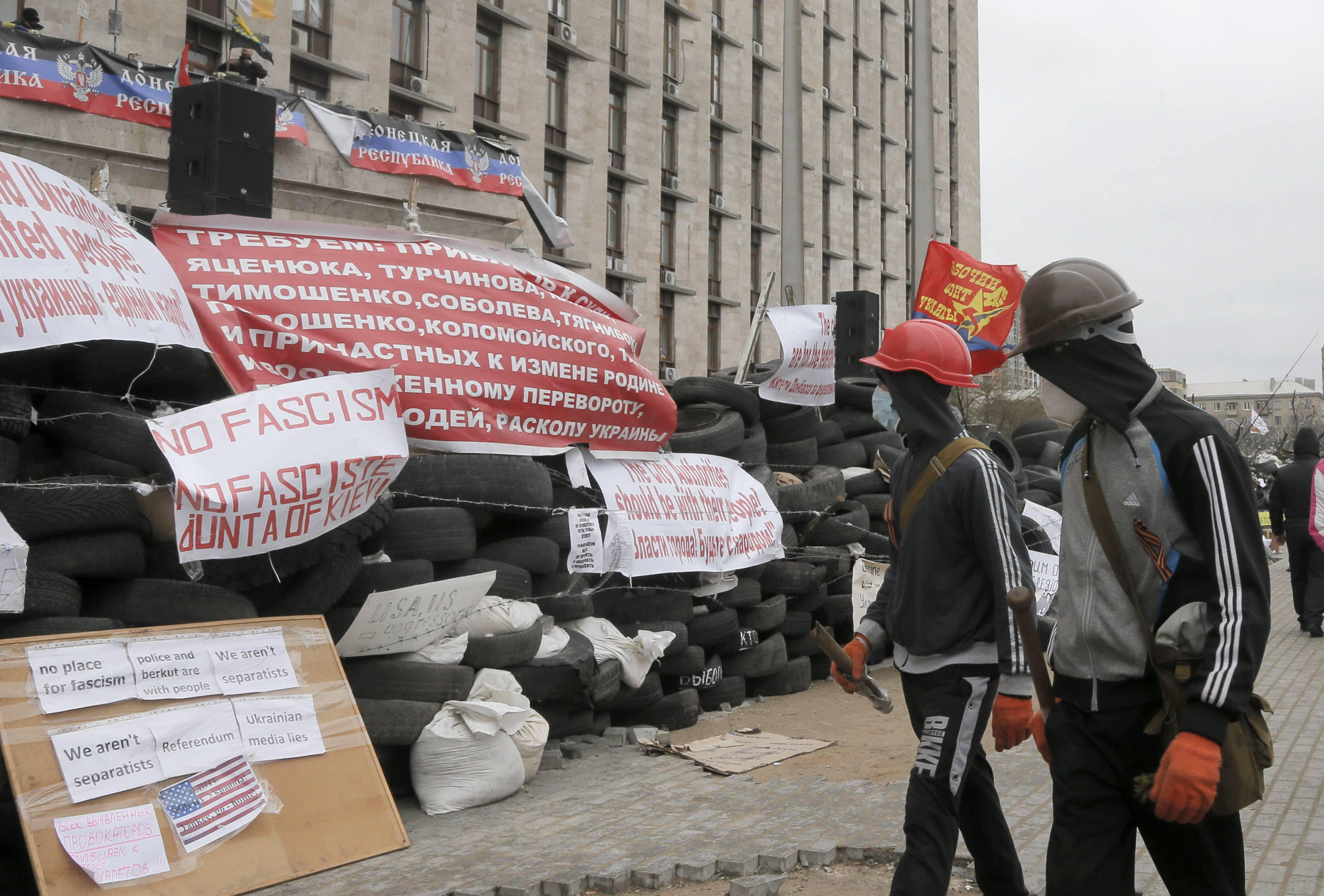 Masked pro-Russian activists pass by a barricade as they guard a regional administration building that they had seized earlier in Donetsk, Ukraine, Friday, April 11, 2014. Ukraine's prime minister on Friday told leaders in the country's restive east that he is committed to allowing regions to have more powers.