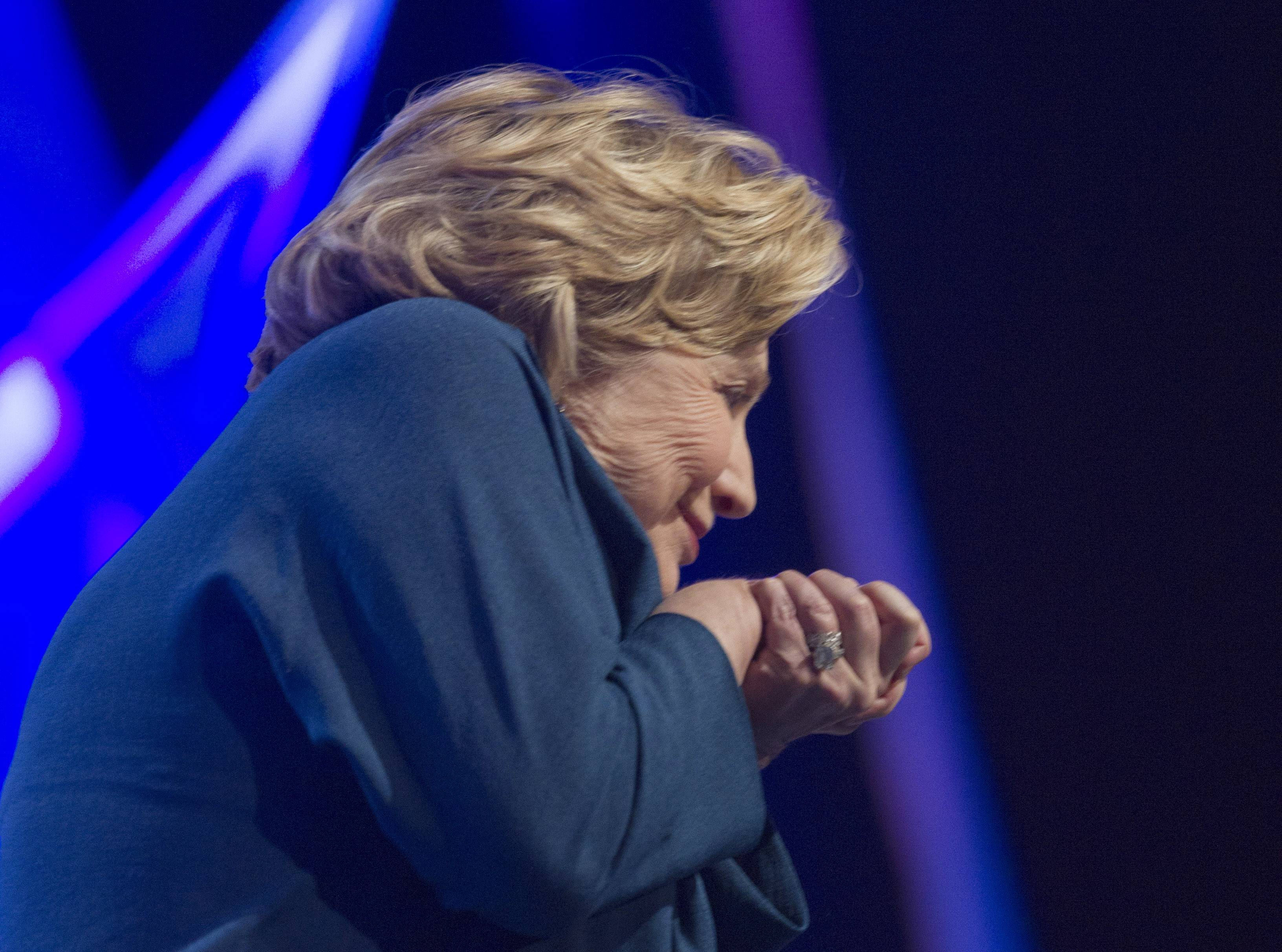 Former U.S. Secretary of State Hillary Rodham Clinton ducks as an object is thrown onstage during an address to members of the Institute of Scrap Recycling Industries during their annual convention at the Mandalay Bay Convention Center, Thursday, April 10, 2014, in Las Vegas.