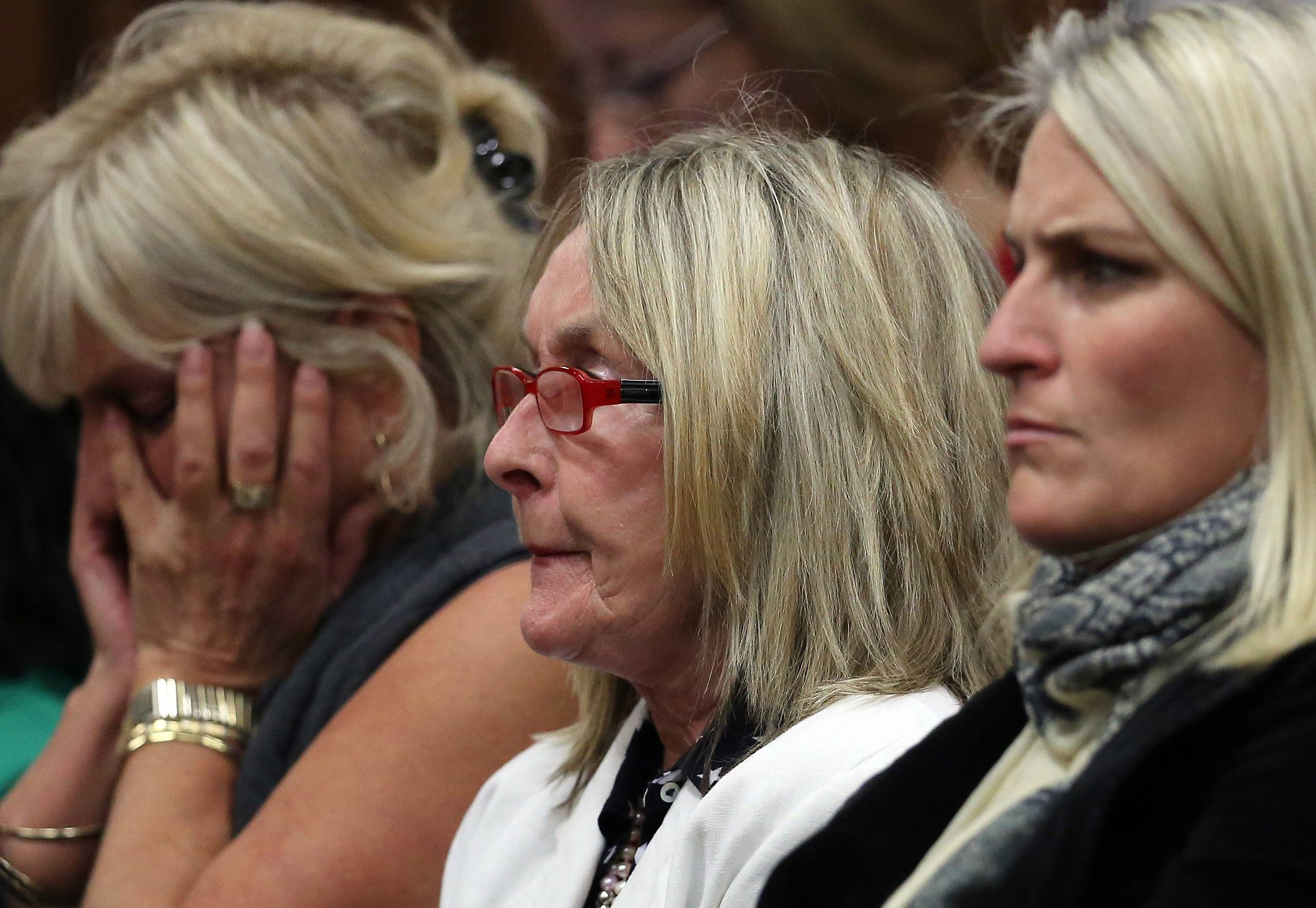 June Steenkamp, center, mother of the late Reeva Steenkamp, listens in the public gallery, as state prosecutor Gerrie Nel questions Oscar Pistorius, in court in Pretoria, South Africa, Friday, April 11, 2014. Pistorius is charged with the murder of his girlfriend Steenkamp, on Valentine's Day in 2013.