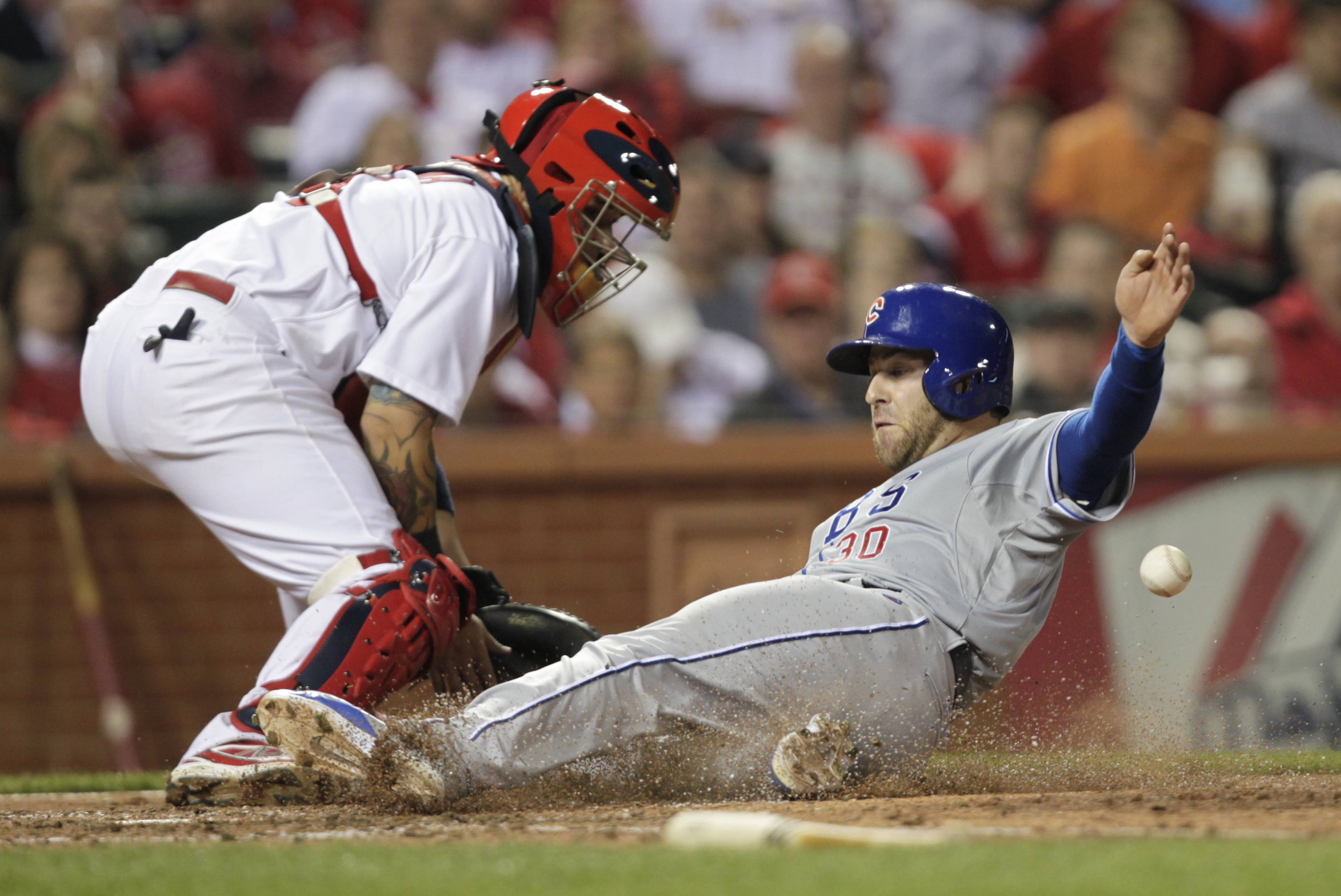 Cubs' Mike Olt (30) scores on a single by Nate Schierholtz as St. Louis Cardinals' Yadier Molina (4) waits for an off-target throw in the eighth inning of a baseball game, Friday, April 11, 2014, in St. Louis.
