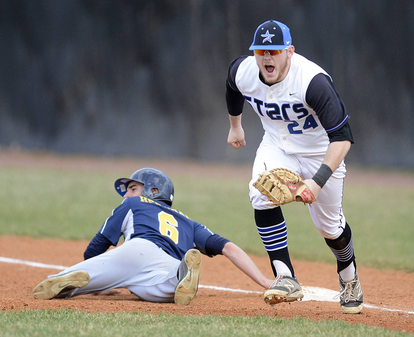 St. Charles North's Jack Dennis celebrates tagging out Neuqua Valley's Zach Herdman at first base for their third out in the second inning on Friday, April 11.