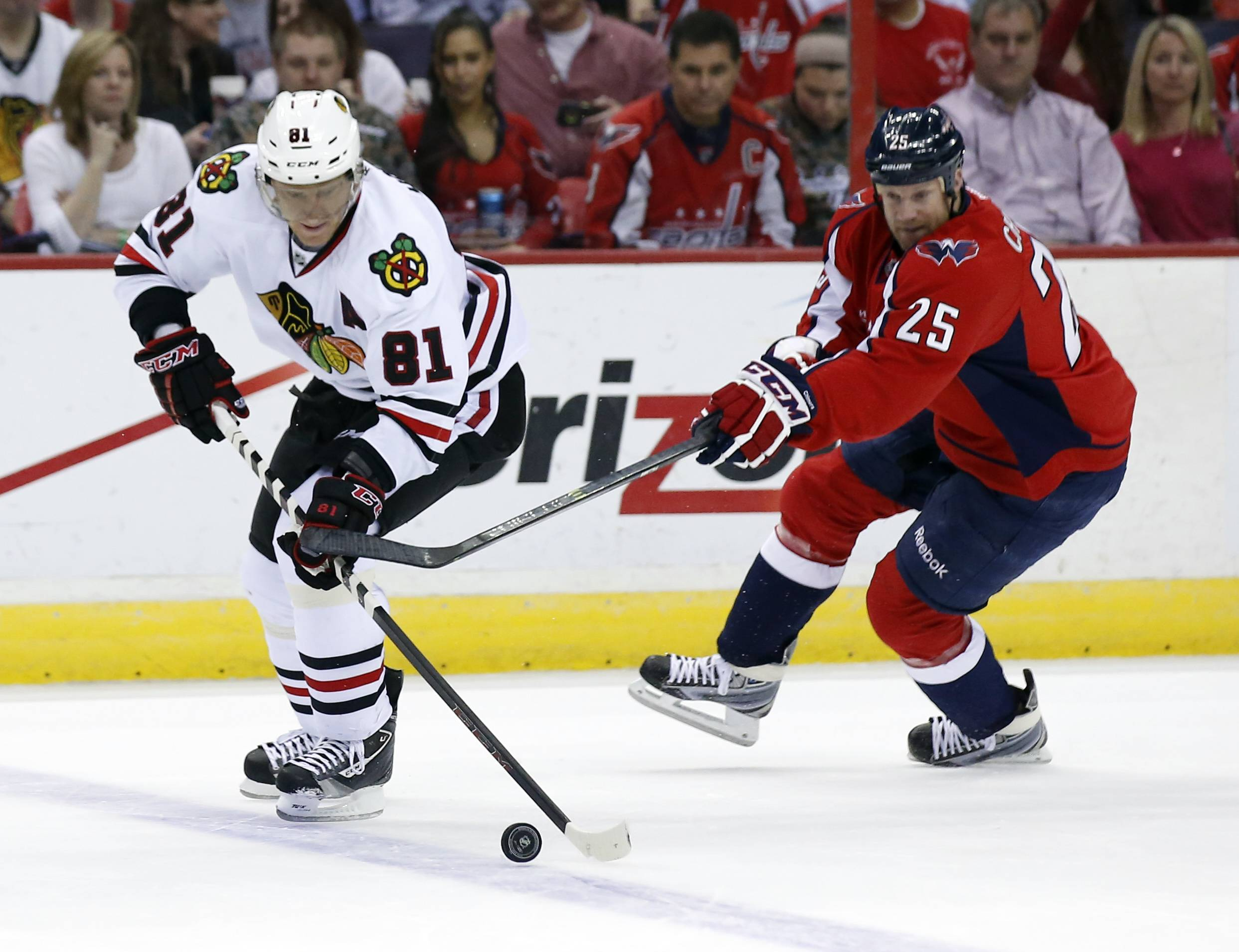 Chicago Blackhawks right wing Marian Hossa (81), from the Czech Republic, skates with the puck as he defended by Washington Capitals left wing Jason Chimera (25) in the first period of an NHL hockey game, Friday, April 11, 2014, in Washington. (AP Photo/Alex Brandon)