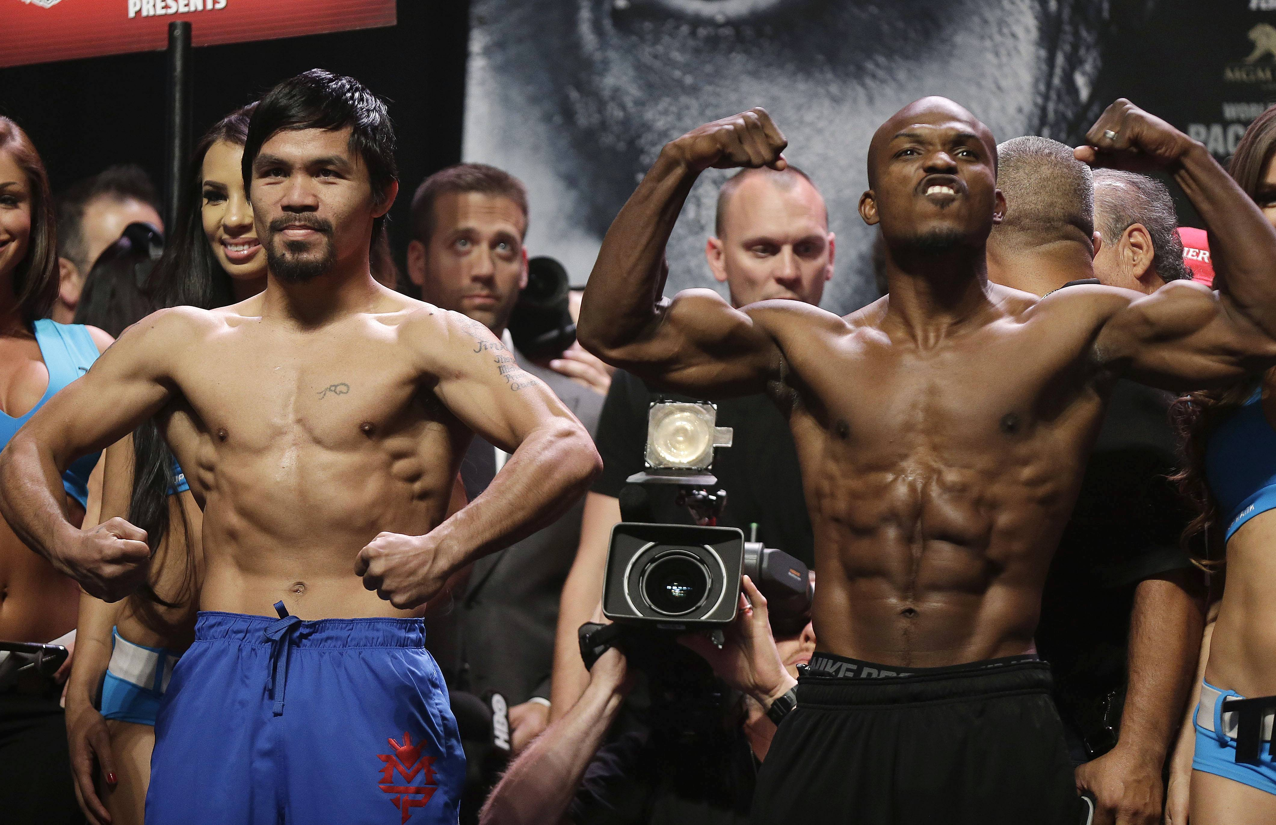 Manny Pacquiao, left, and Timothy Bradley pose for photos following after the weigh-in for Saturday's WBO welterweight championship boxing match, Friday, April 11, 2014, in Las Vegas. (AP Photo/Isaac Brekken)