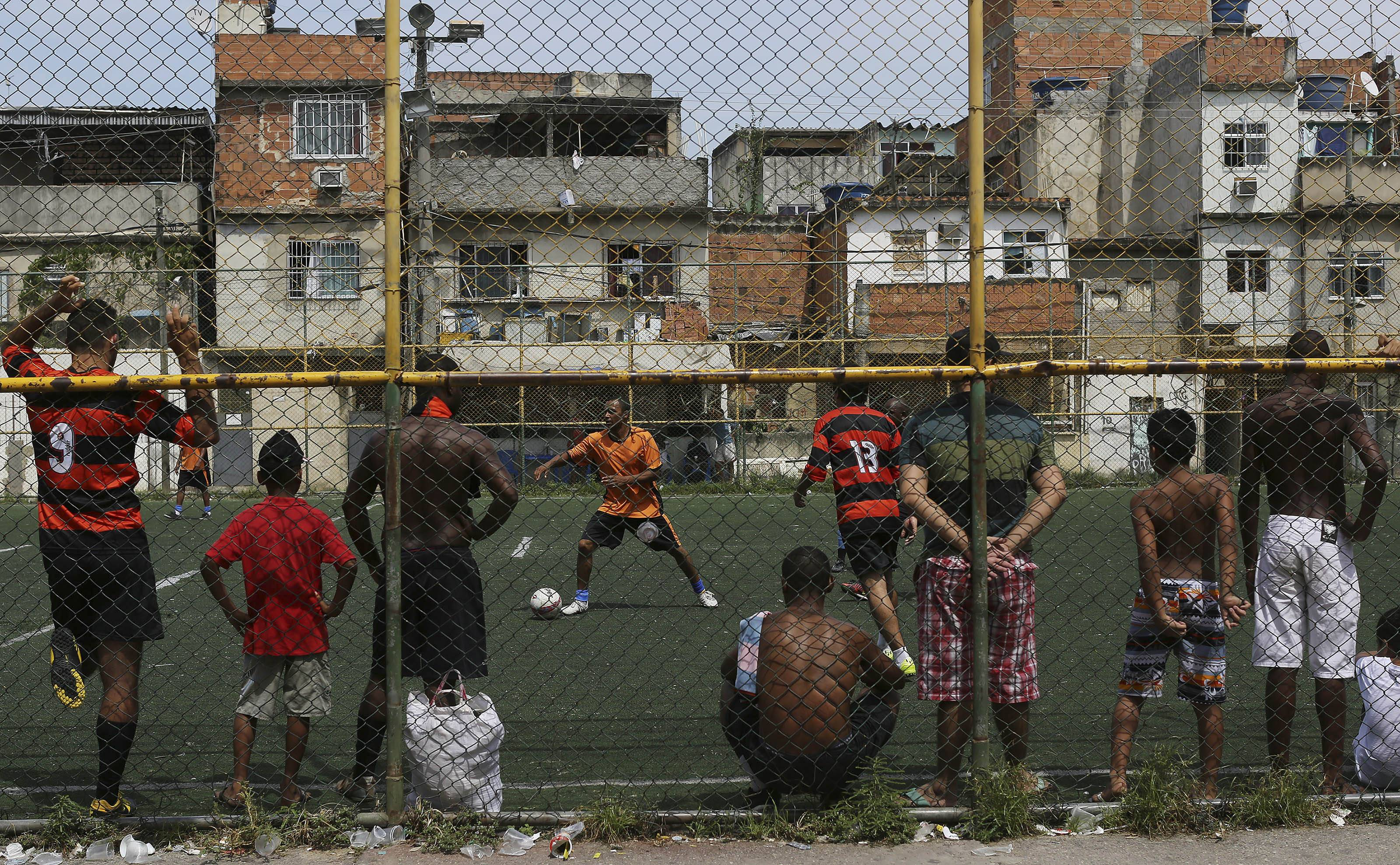 "Residents play soccer at the Nova Holanda, part of the Mare slum complex in Rio de Janeiro, Brazil, Sunday, March 30, 2014. The Mare complex of slums, home to about 130,000 people and located near the international airport, is the latest area targeted for the government's ""pacification"" program, which sees officers move in, push out drug gangs and set up permanent police posts. (AP Photo/Leo Correa)"