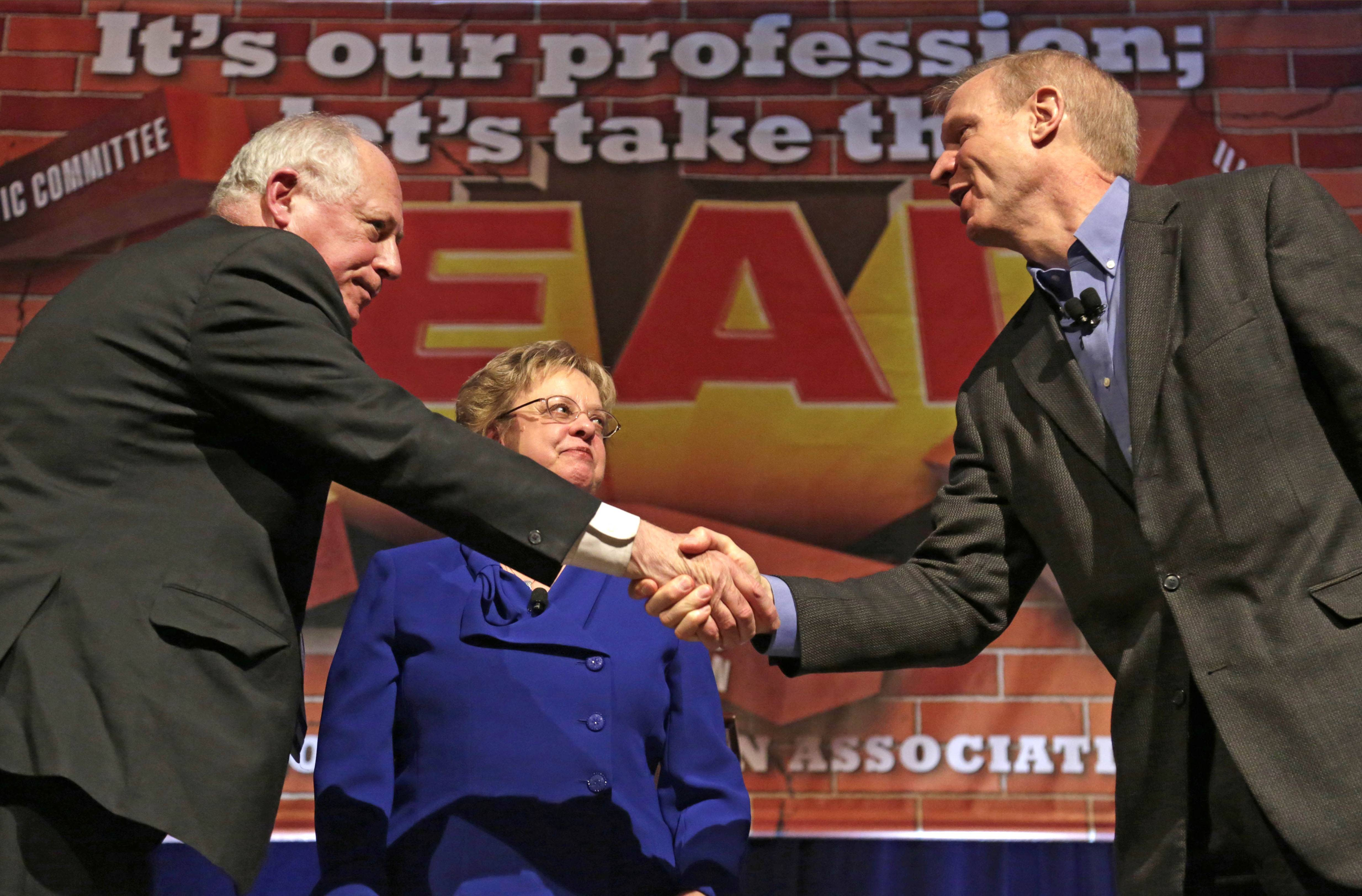 Gov. Pat Quinn, left, and his Republican rival, Bruce Rauner, shake hands after they appeared together Friday during the annual meeting of the Illinois Education Association in Chicago. Association President Cinda Klickna, who moderated the event, stands between them.