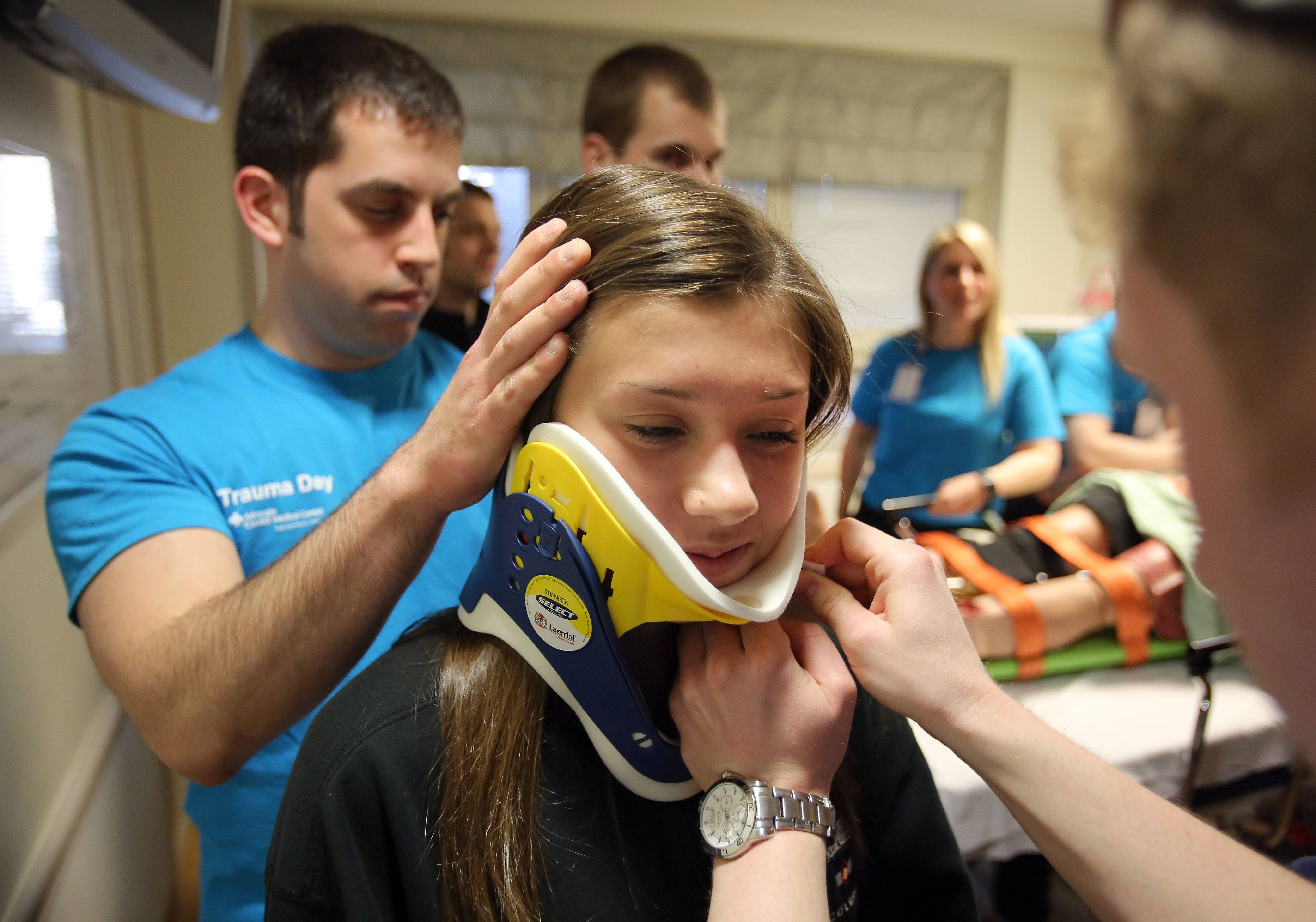 Libertyville High School Emily Elfering tries on a neck brace with the help of paramedic students Dan Cheval, left, and Kevin Learch during Trauma Day at Advocate Condell Medical Center Friday in Libertyville