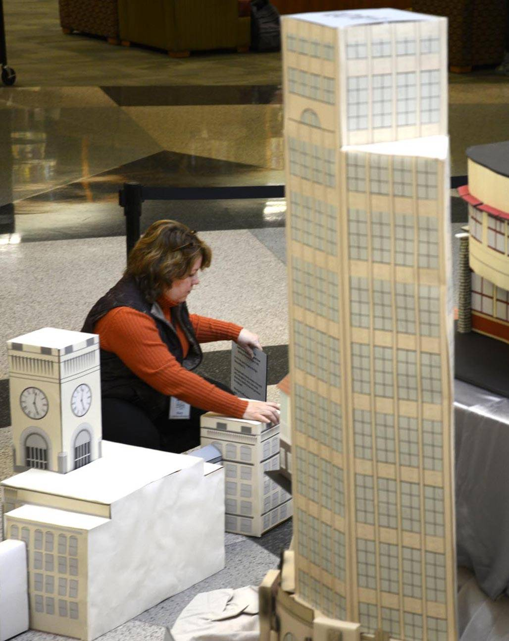A model of the Elgin Tower Building stands taller than Mary Amici-Kozi, its creator. She works in the creative services department of the Gail Borden Public Library.