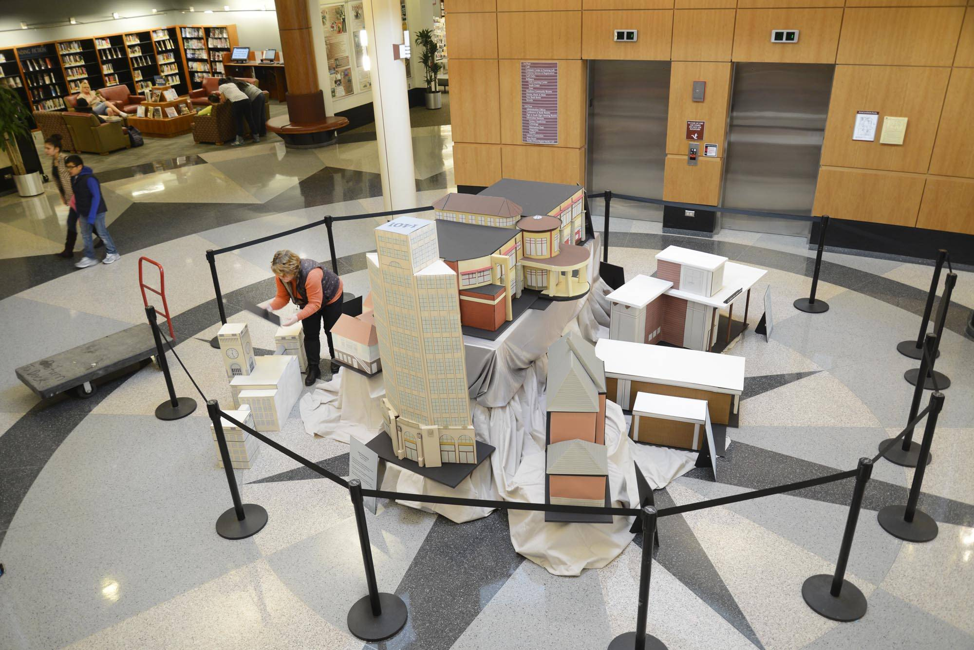 Mary Amici-Kozi sets up a large display of iconic Elgin buildings in the lobby area of the Gail Borden Public Library. She works in the creative services department as a graphic artist.