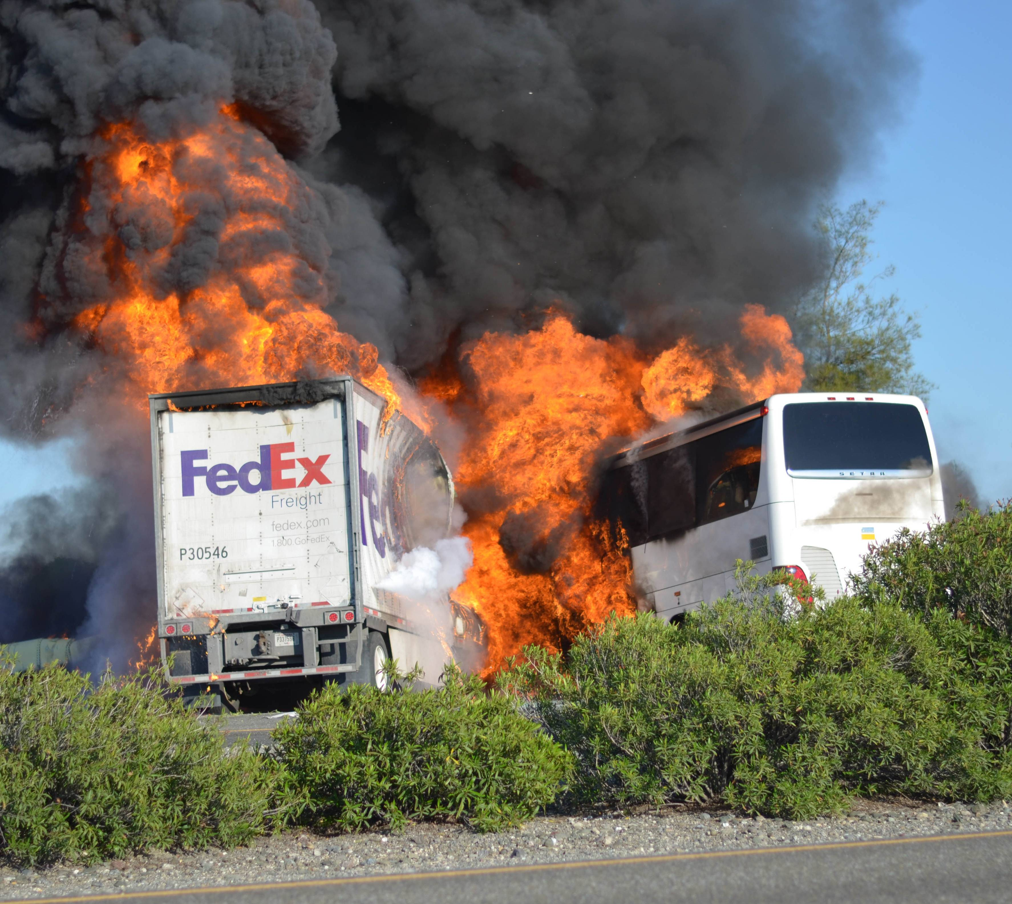 Massive flames engulf a tractor-trailer and a tour bus just after they collide on Interstate 5, Thursday April, 10, 2014, near Orland, Calif. At least 10 people were killed in the crash, authorities said.