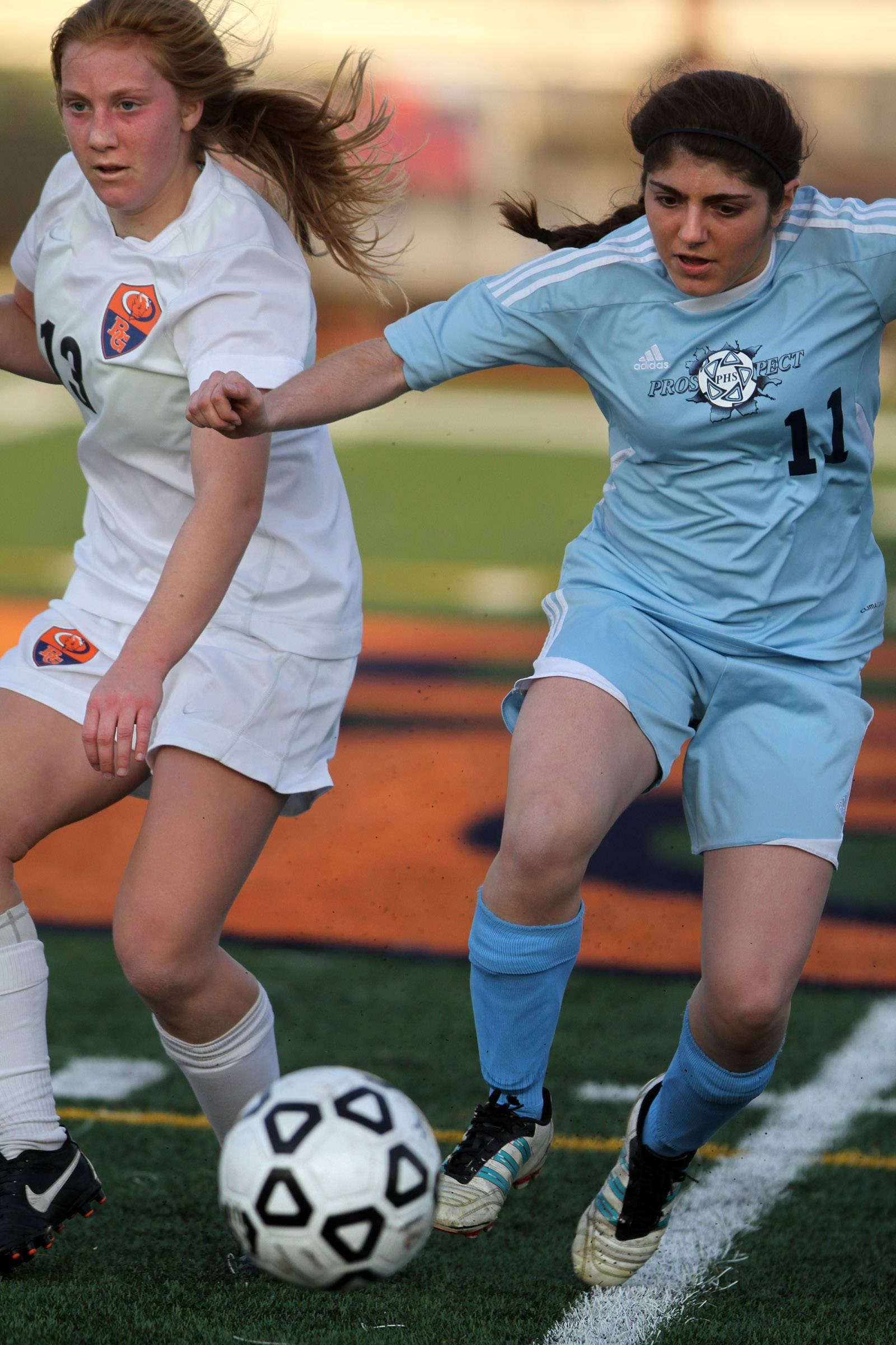 Prospect defender Danielle Hamzeloo passes the ball with Buffalo Grove forward Kelli Zickert trailing on Friday at Buffalo Grove.