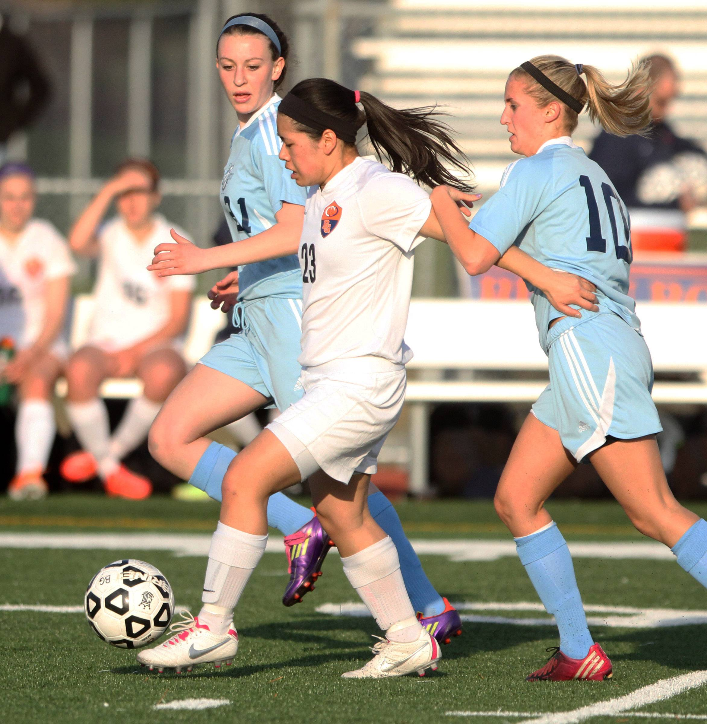 Buffalo Grove defender Elizabeth Chan passes the ball while sandwiched between Prospect forward Alyson Kobler, left, and forward Emily Novak on Friday at Buffalo Grove.