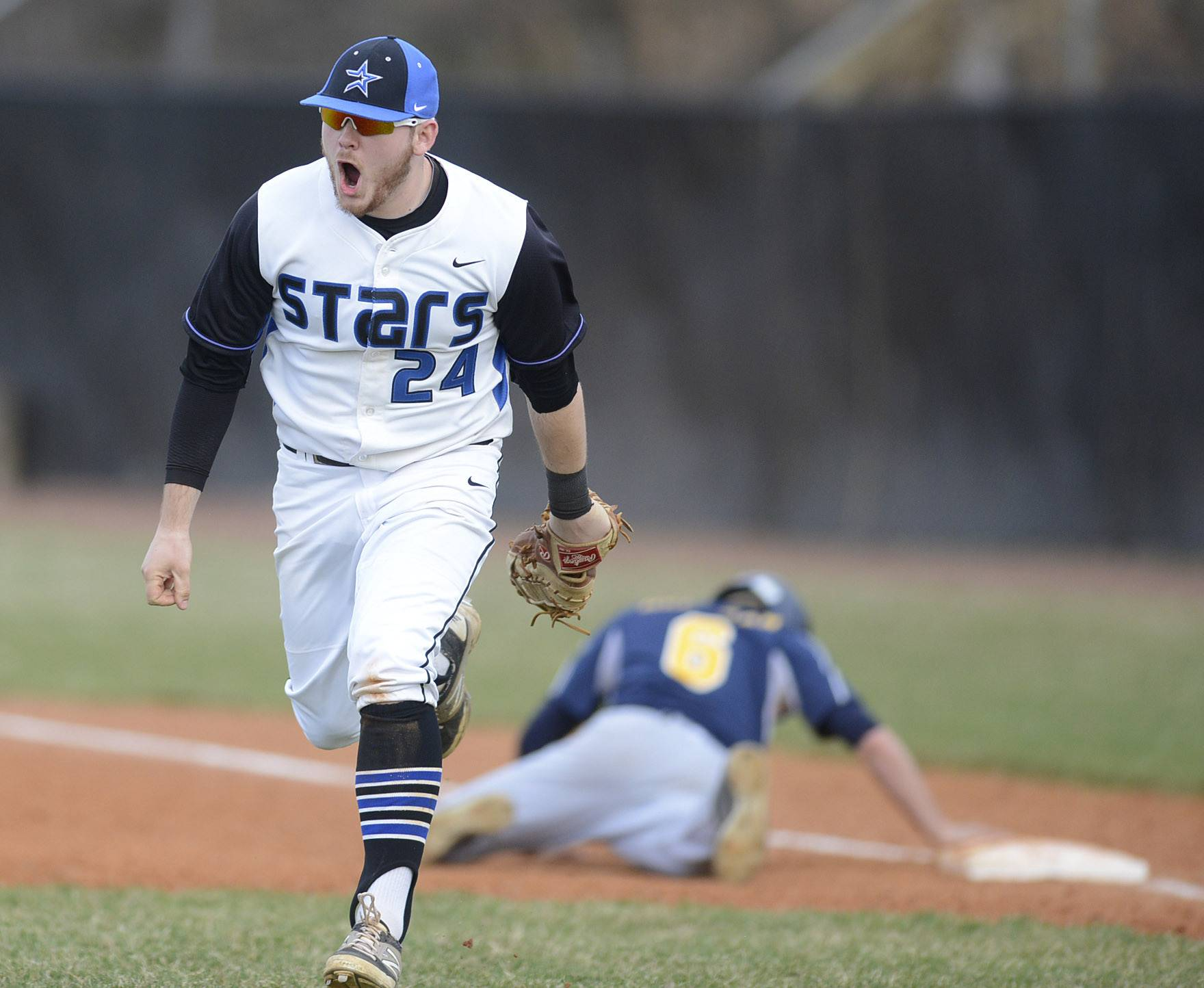 St. Charles North's Jack Dennis heads back to the dugout celebrating tagging out Neuqua Valley's Zach Herdman at first in the second inning on Friday, April 11.