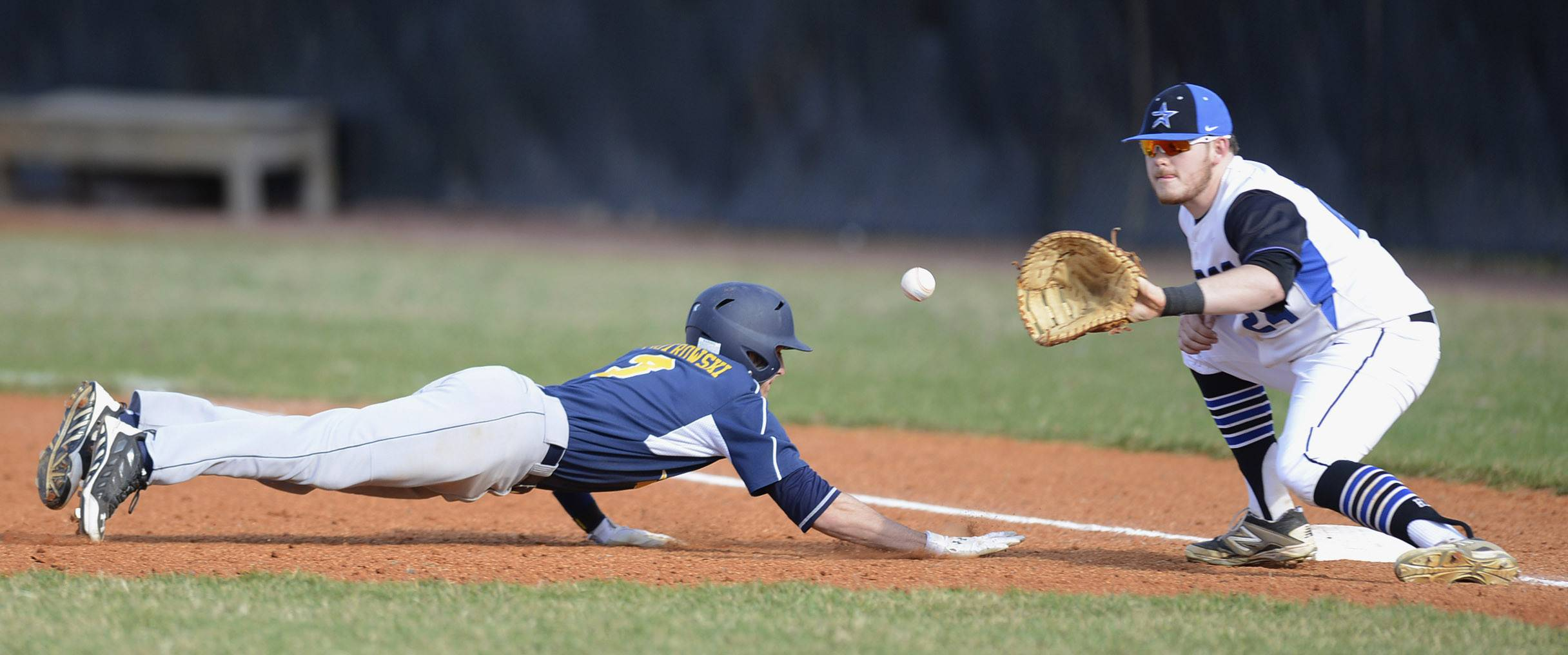 Neuqua Valley's Josh Piotrowski slides back safely to first base and St. Charles North's Jack Dennis in the first inning on Friday, April 11.