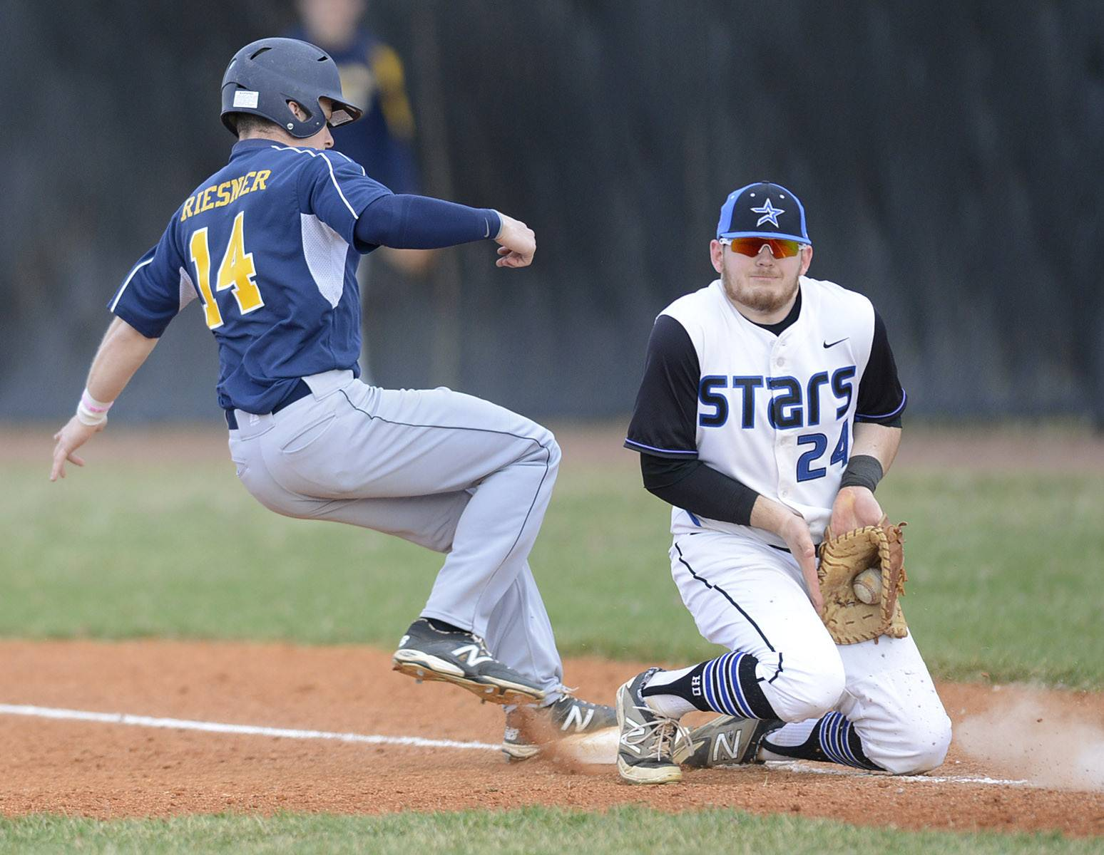 Neuqua Valley's Mike Riesner is safe back on first base from St. Charles North's Jack Dennis in the third inning on Friday, April 11.