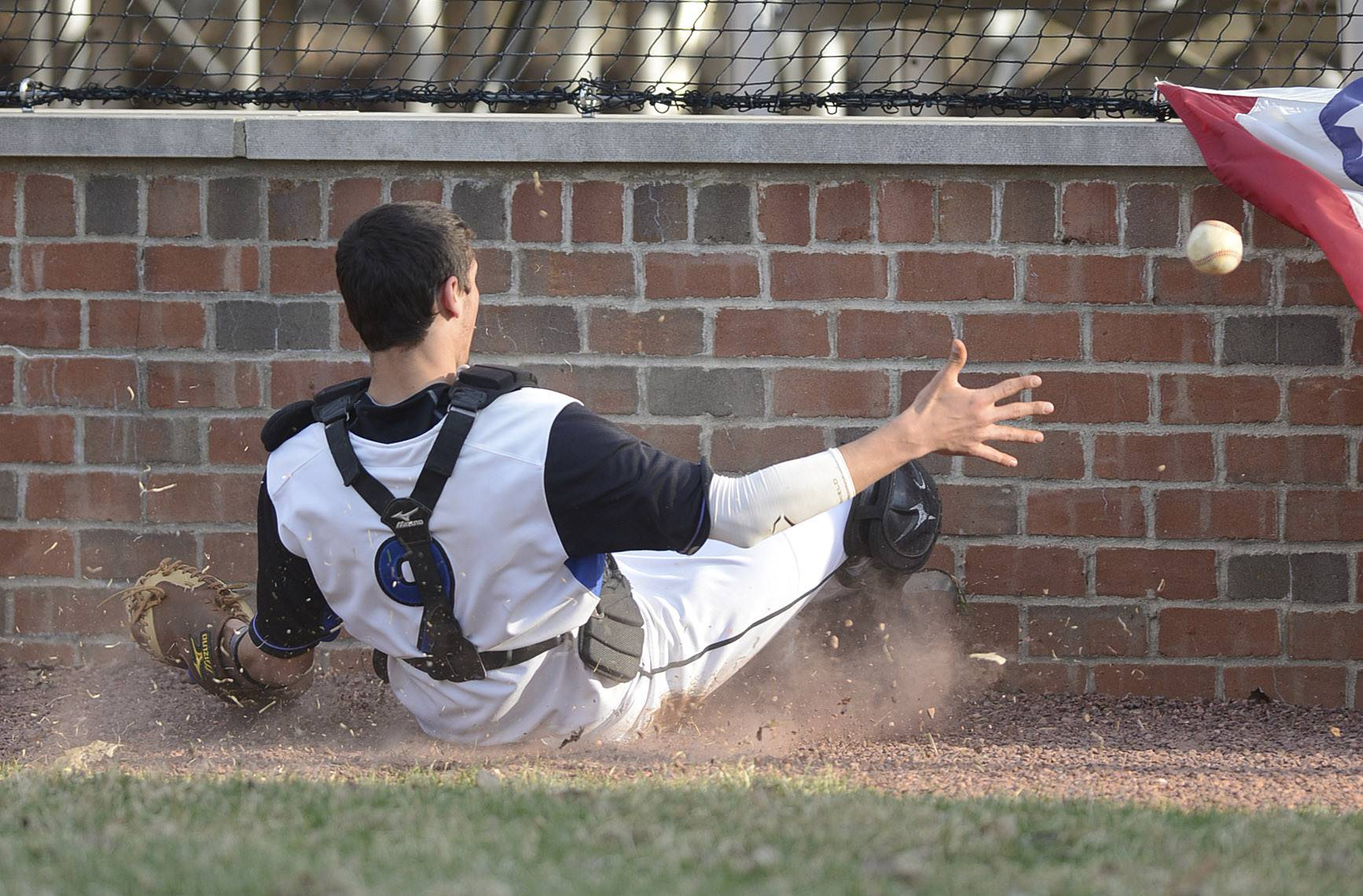 St. Charles North's Kyle Khoury slides into the wall attempting to grab a ball in the fourth inning on Friday, April 11.