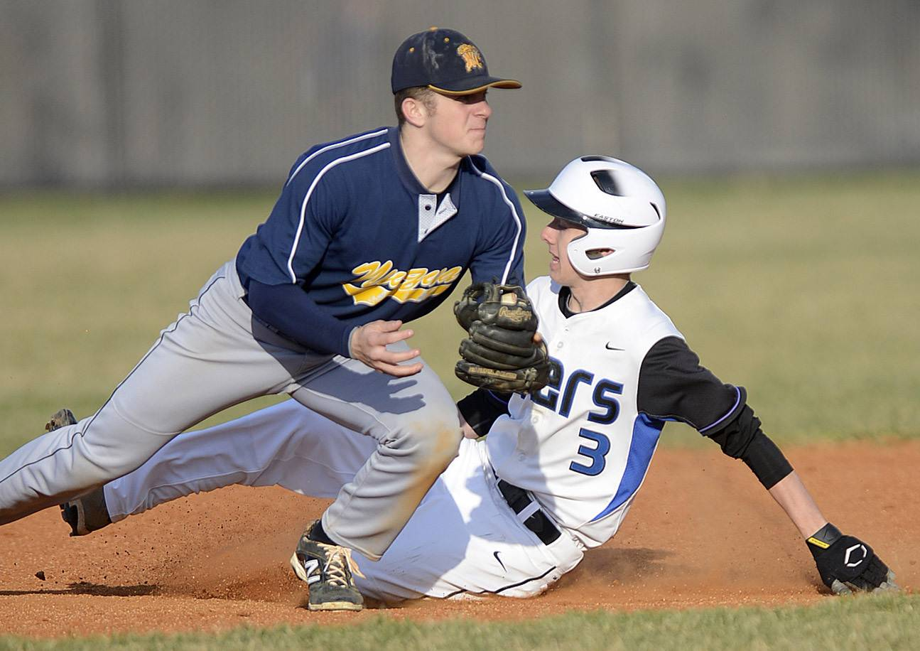 St. Charles North's Jake Jozefowicz slides into second base past Neuqua Valley's Mike Riesner but a foul ball is called in the fourth inning on Friday, April 11.