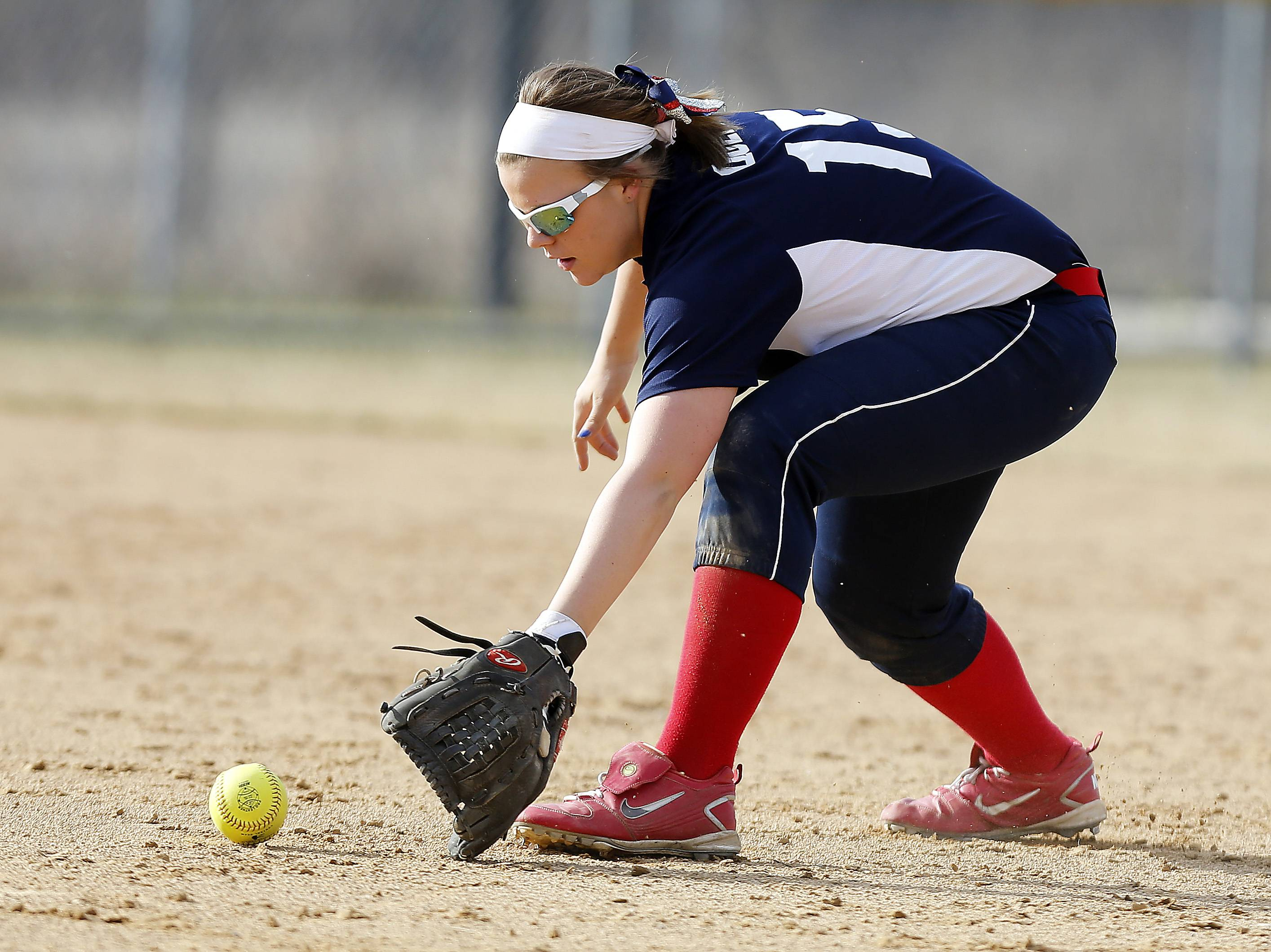 South Elgin's Demi Queen scoops up a grounder to throw out St. Charles North's Erin Nemetz during the second inning at South Elgin on Friday.