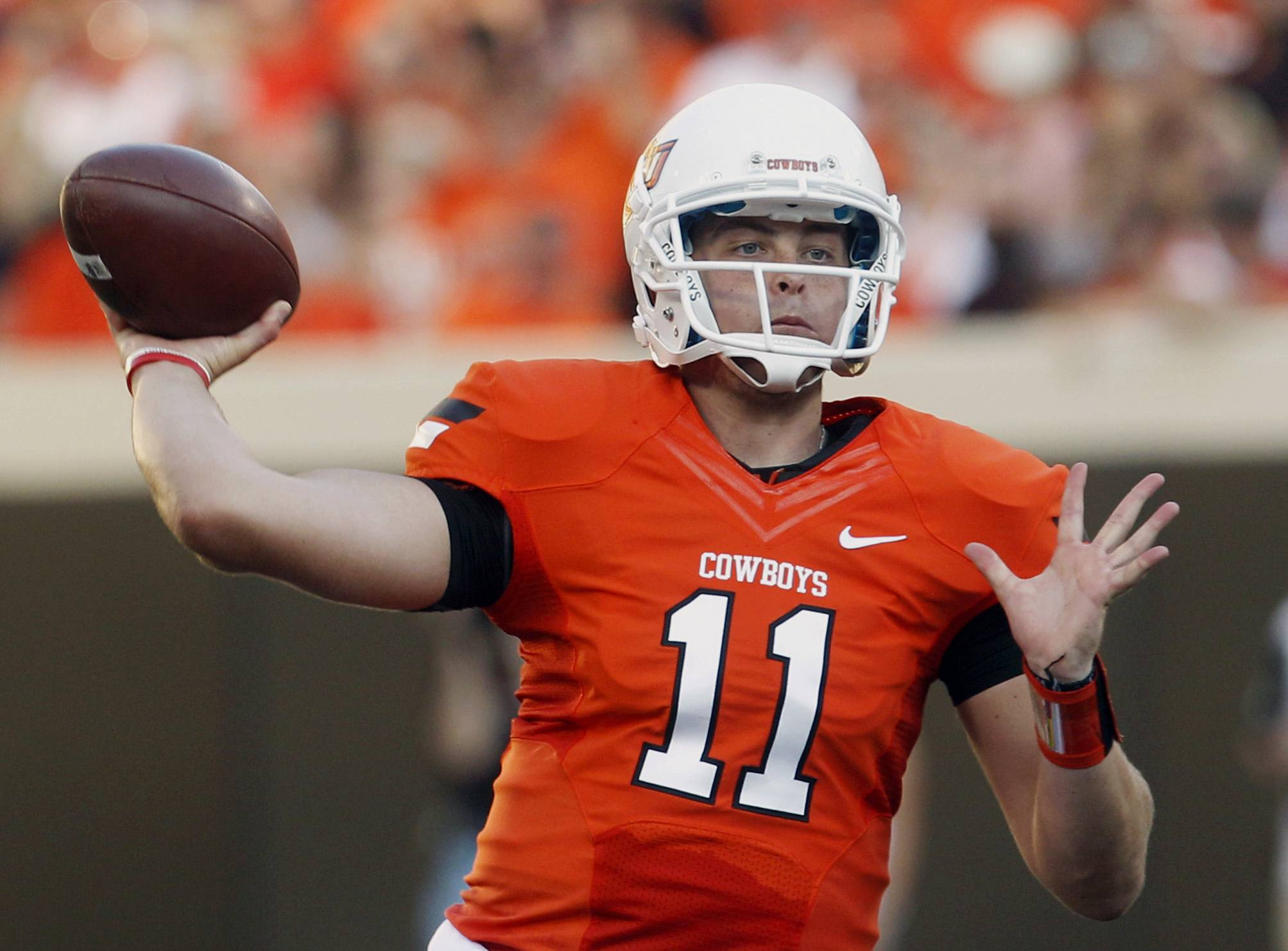 FILE - In this Sept. 1, 2012 file photo, Oklahoma State quarterback Wes Lunt throws against Savannah State during an NCAA college football game in Stillwater, Okla. Illinois head coach Tim Beckman says he's in no hurry to name a starting quarterback and that the competition between the three potential candidates to succeed Nathan Scheelhaase is wide open. Lunt brings a skill set and a pedigree that the Illini haven't seen in a while. The tall, strong-armed quarterback sat out last season after transferring from Oklahoma State.
