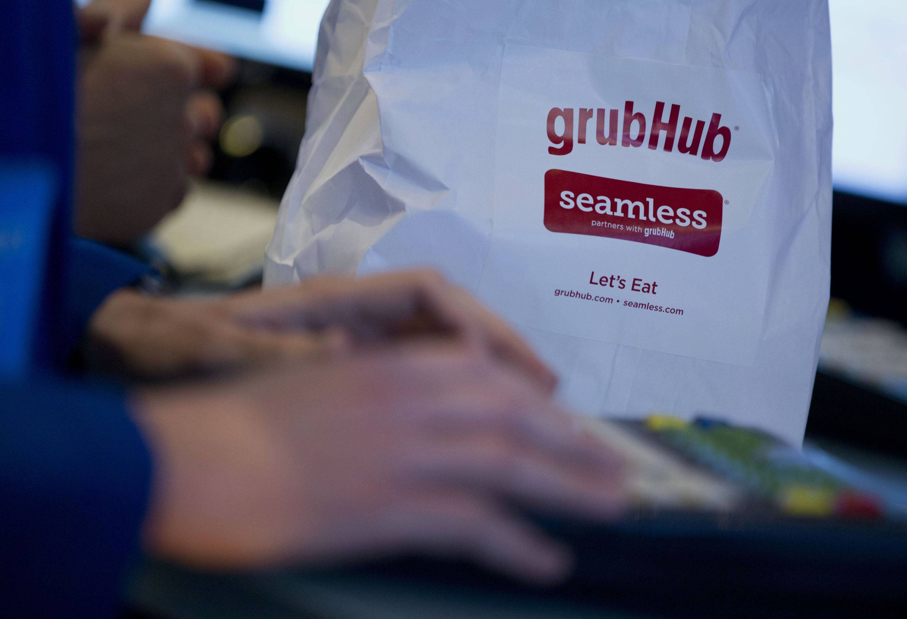 A trader works next to a GrubHub Inc. paper bag on the floor of the New York Stock Exchange in New York.