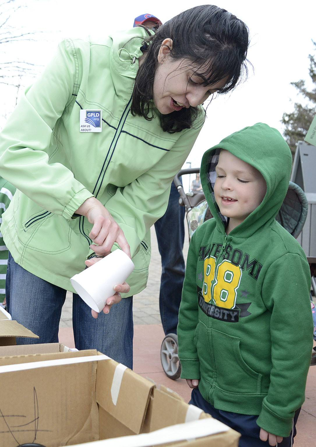 Kimberly Gotches of the Geneva Public Library shows the recycling number code on the bottom of a Styrofoam cup to Connor McInerney of Geneva Saturday at the library's Earth Day booth at Peck Farm Park in Geneva.