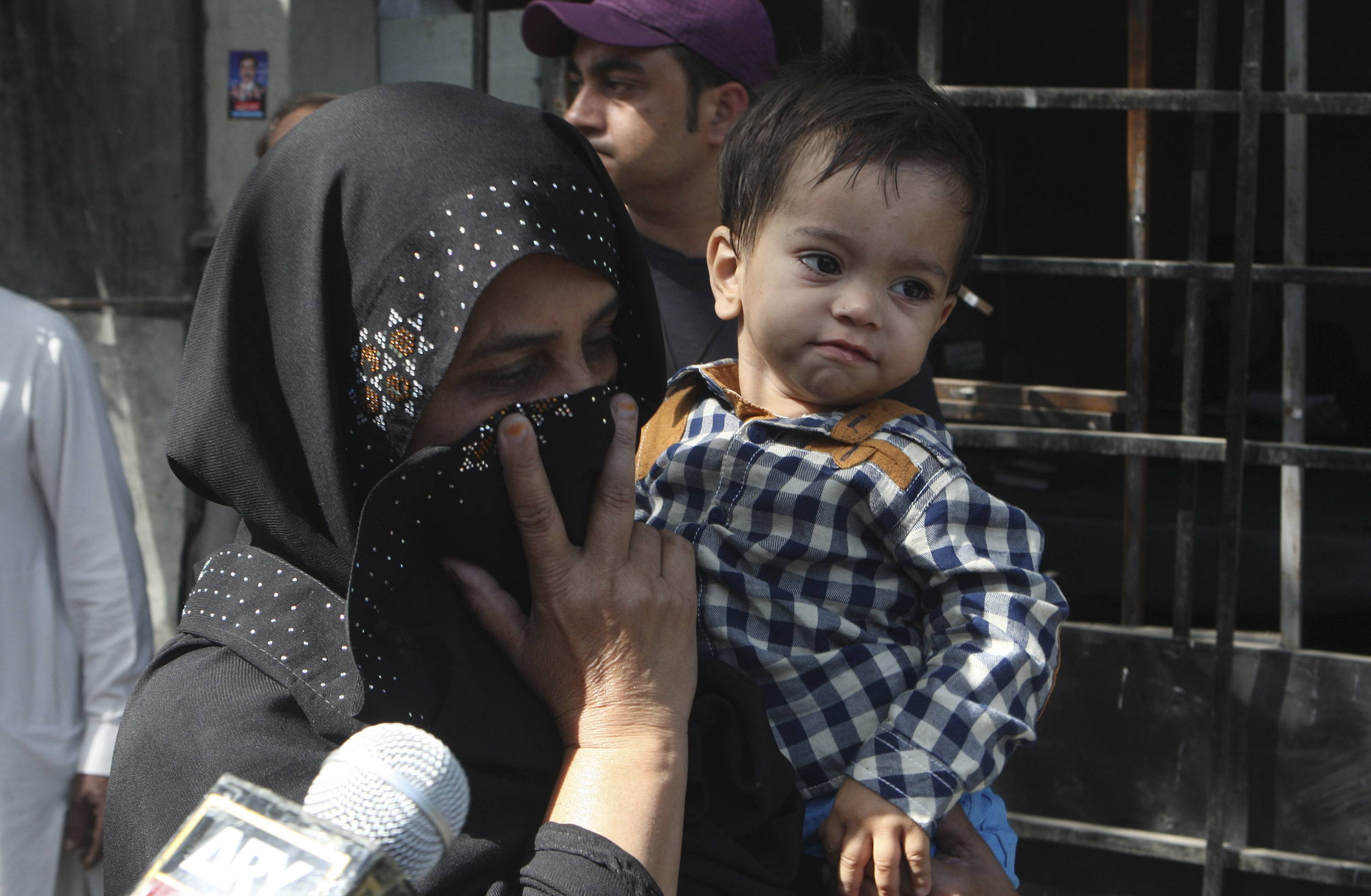An unidentified family member holds a nine-month-old boy, trying to avoid media Saturday as they leave after the boy's court appearance in Lahore, Pakistan.