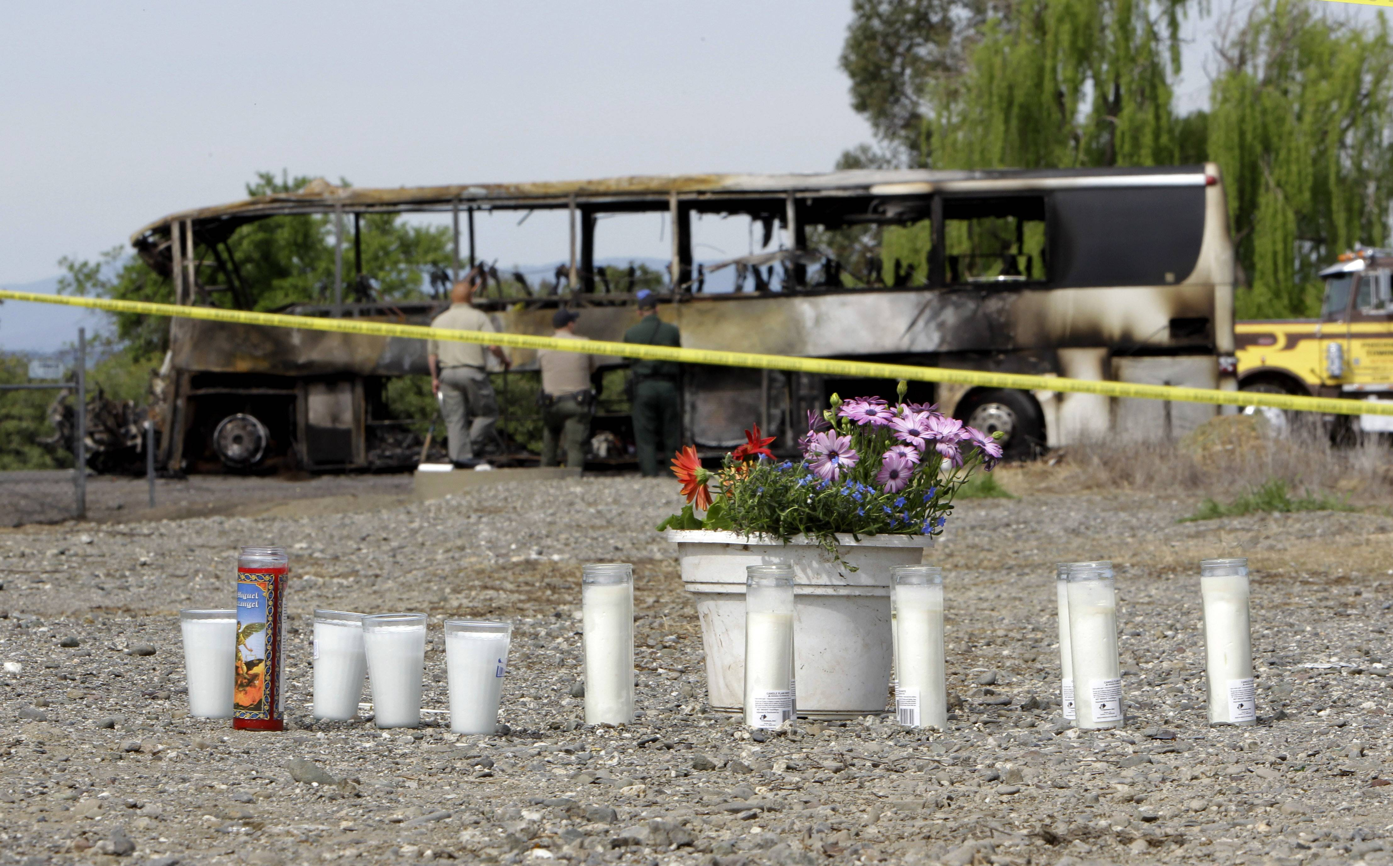 Candles and flowers are seen at a make-shift memorial, Friday, April 11, 2014, for the victims of a multi-vehicle accident that included a tour bus and a FedEX truck crashed on Interstate 5 in Orland, Calif. Ten people were killed and dozens injured in the fiery crash, Thursday, between the truck and a bus seen in background, carrying high school students on a visit to a Northern California College.