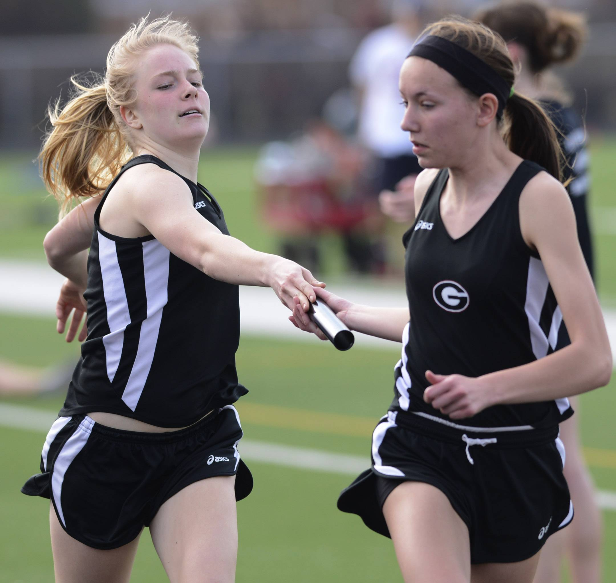Grant's Brooke Drabek, left, passes the baton to Madison Romig during the 4x800-meter relay during Saturday's track meet in Fox Lake.