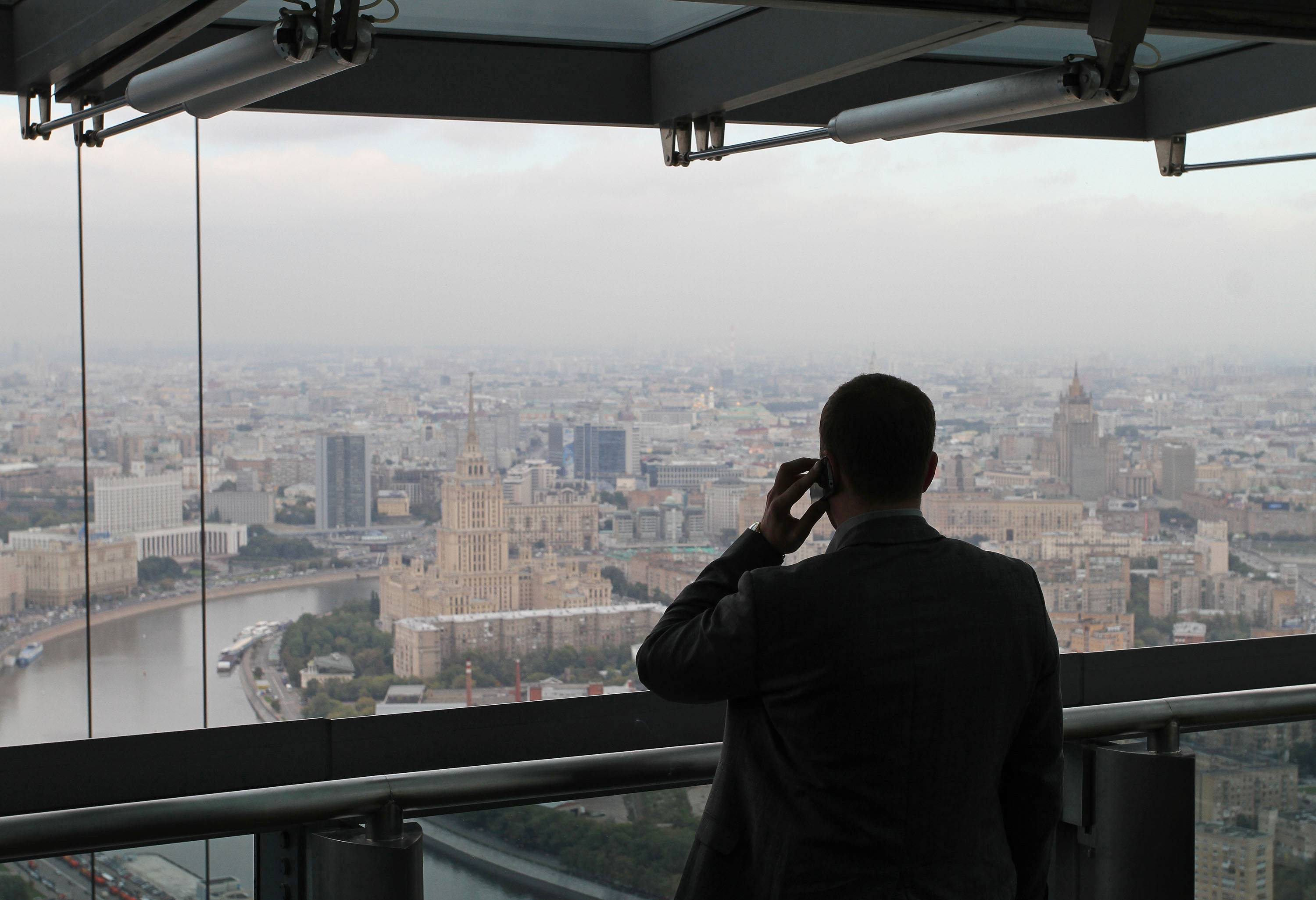 A visitor looks at the city skyline Tuesday as he speaks on a mobile phone from a viewing deck in the Federation Tower at the Moscow International Business Center, also known as Moscow-City, the capital's new commercial district in Moscow, Russia's central bank unexpectedly cut its repurchase rate and raised the rate it pays on deposits to avert a potential ruble shortage in money markets.