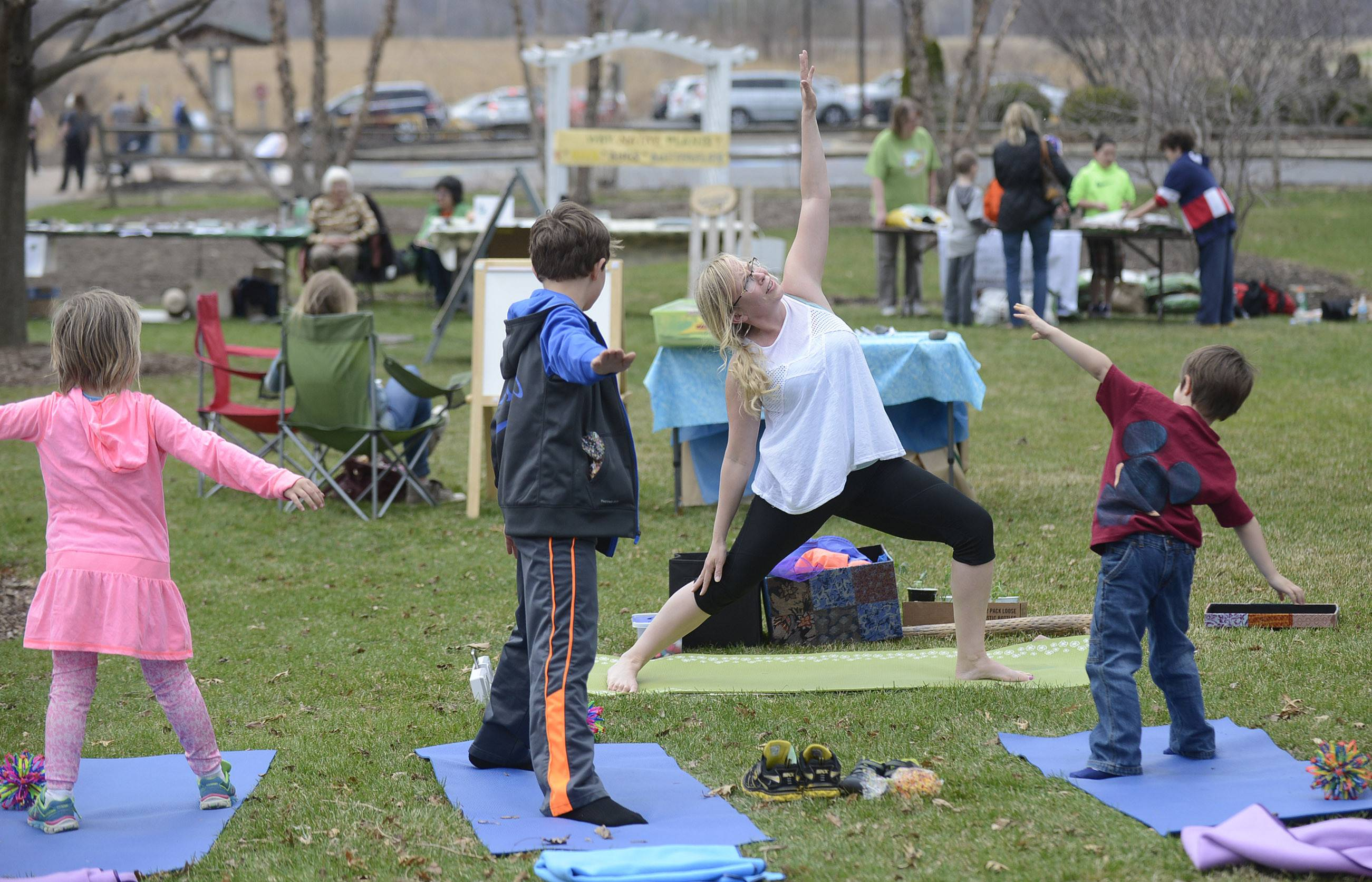 Shelley Ost, owner of Karma Yoga Child of Geneva, takes children through yoga poses Saturday at Peck Farm Park's Earth Day in Geneva.