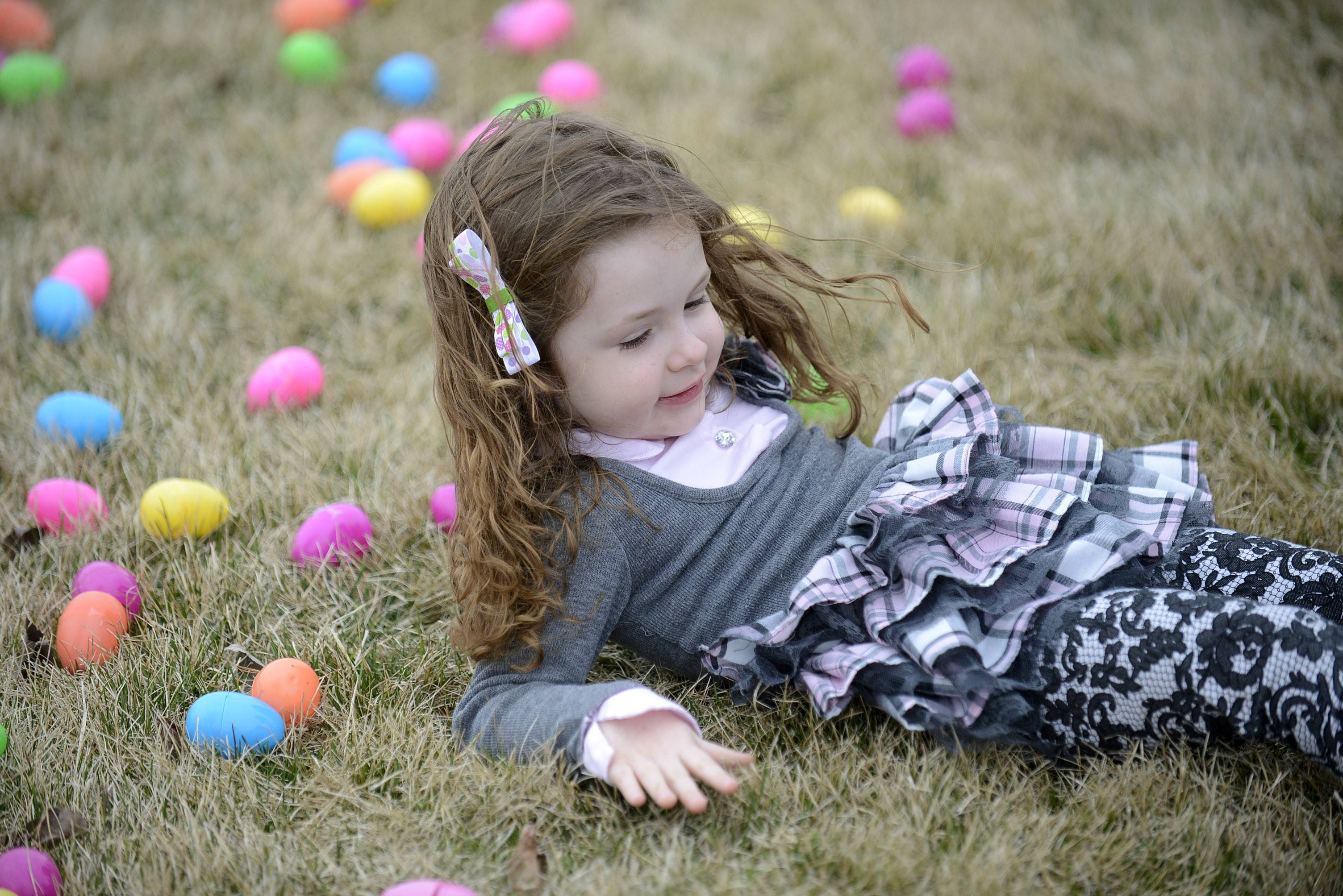 Jordan Cote, 3, of Geneva, rests among plastic eggs after having her picture taken by her parents Saturday at Faith Baptist Mill Creek Creek Church's egg hunt in Geneva.