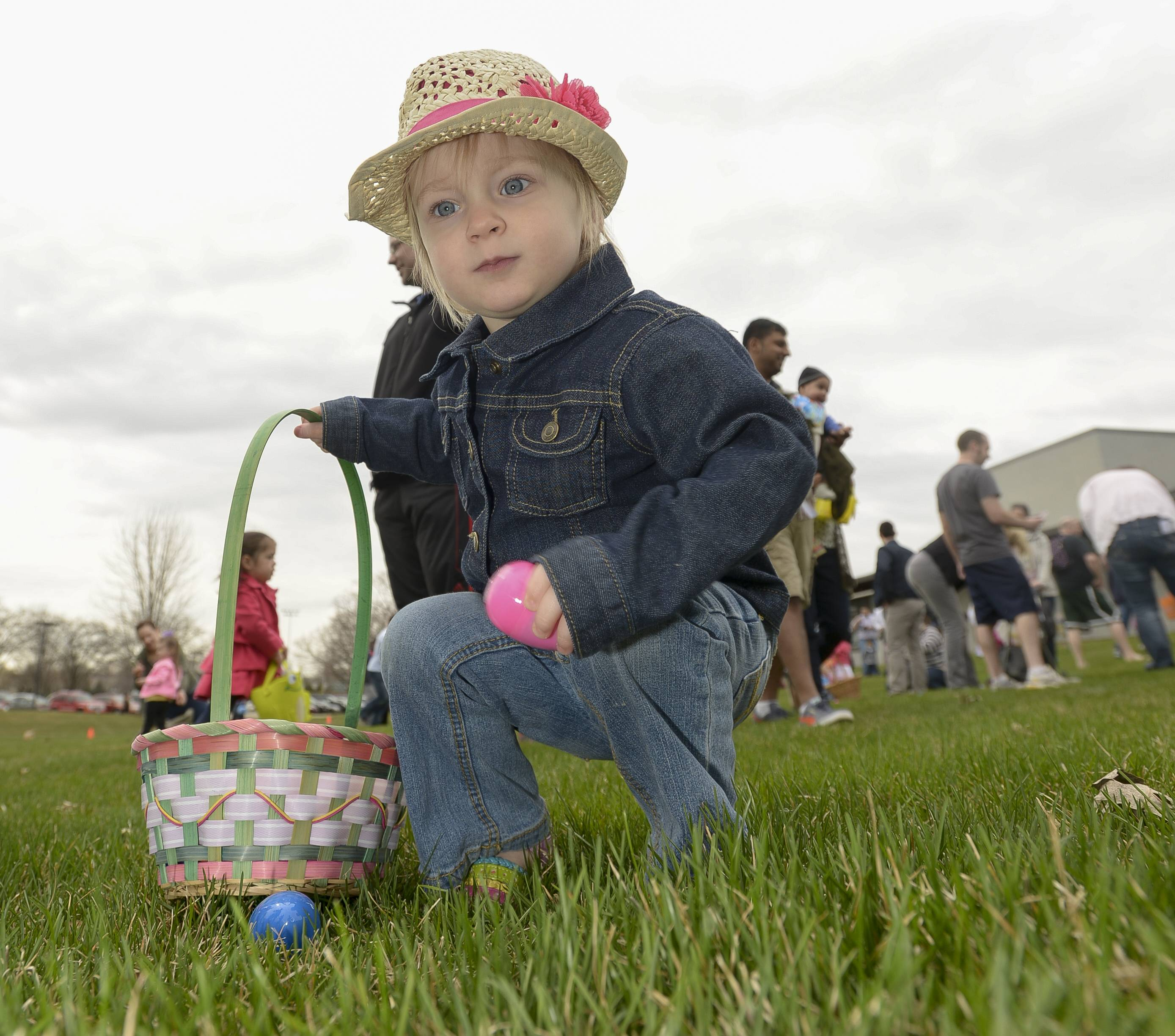 Rebecca Larsen, 2, of Lisle, collects a plastic egg during an Easter egg hunt Saturday at Lisle's Community Park.