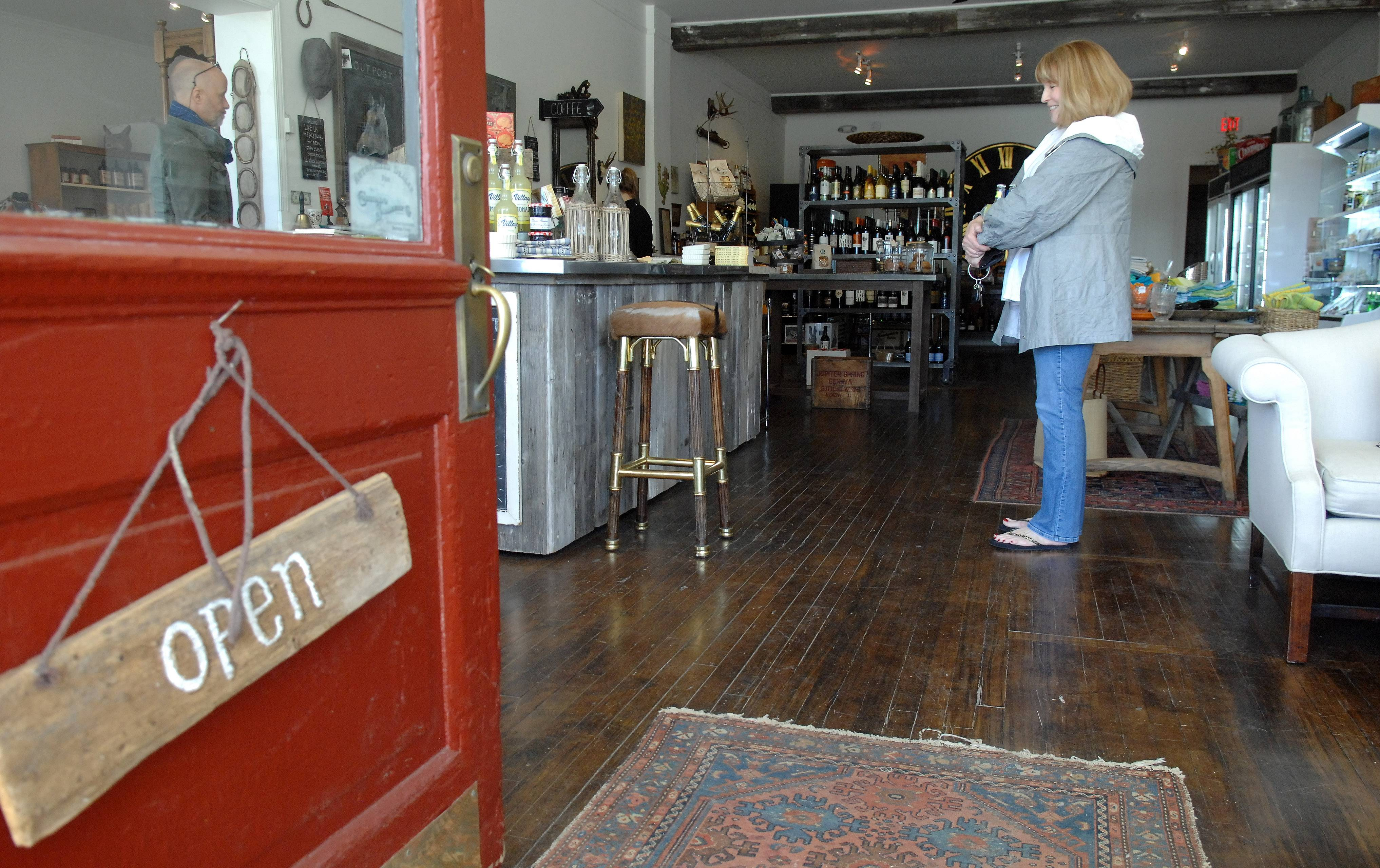 Karen Lando of St. Charles talks with owner Joe Vajarsky after making a purchase at the Outpost General Store in Wayne. Vajarsky and his wife, Caroline Scheeler, opened the store last September.