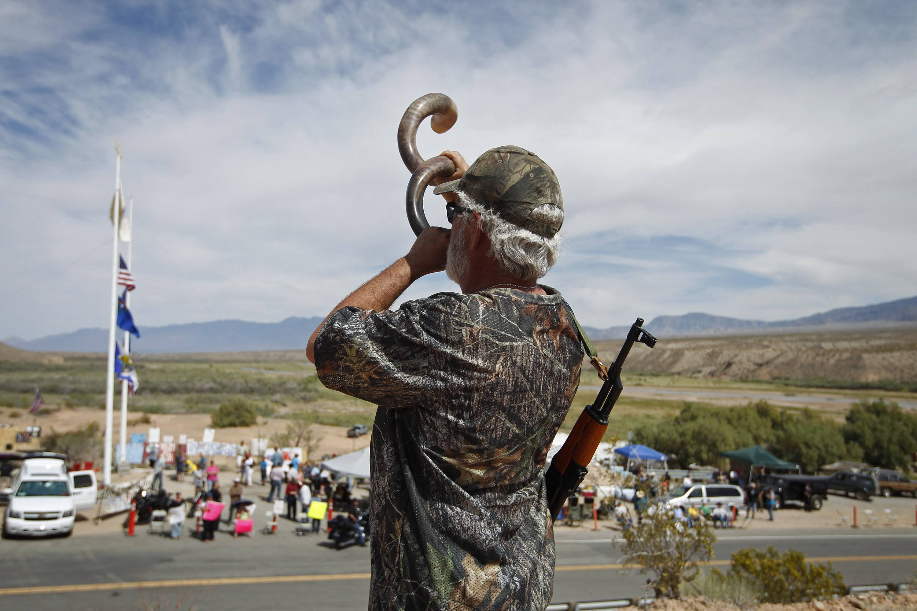 Brand Thornton, of Las Vegas, blows a shofar Friday on a hillside above a protest area near Bunkerville, Nev.