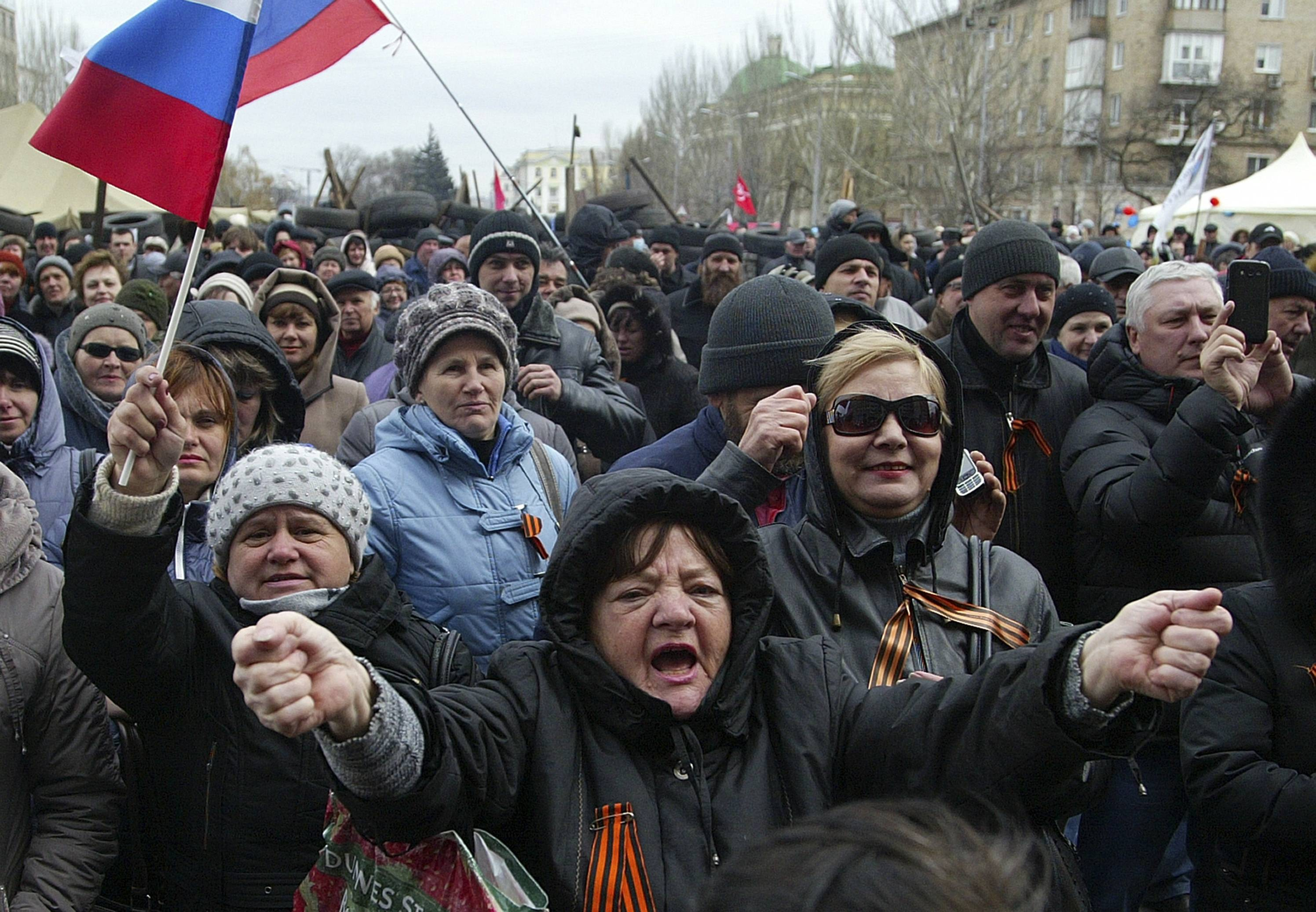 Pro-Russian protesters holding Russian flags gather at the regional administration building in Donetsk, Ukraine, Saturday, April 12, 2014. Protesters, who have held the administration building in Donetsk since Sunday, initially called for a referendum on secession but later reduced the demand to a vote on autonomy within Ukraine with the possibility of holding another later on whether to join Russia.